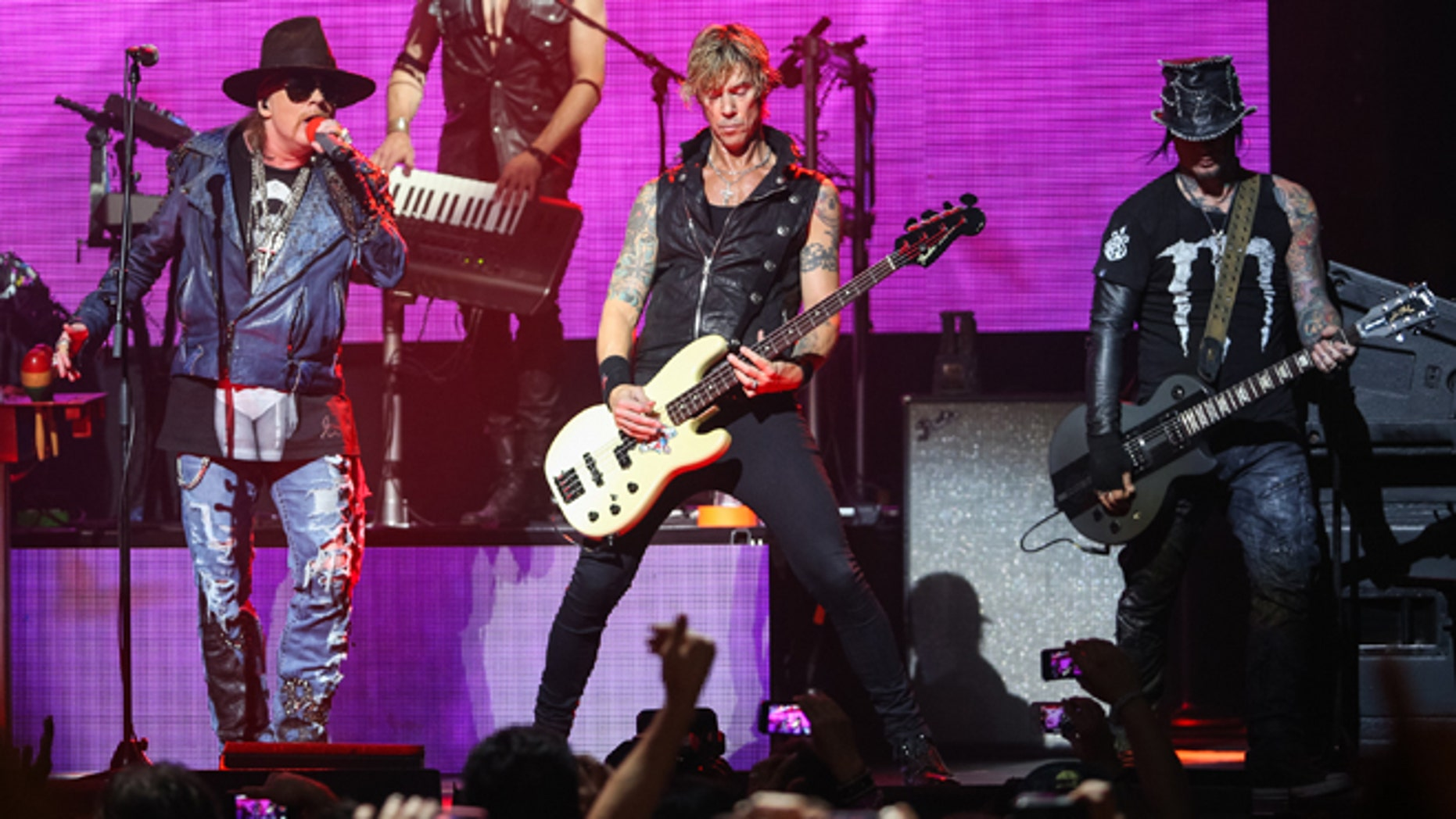April 23, 2014 file photo, Axl Rose, from left, Duff McKagan and DJ Ashba of Guns N' Roses perform in Los Angeles.