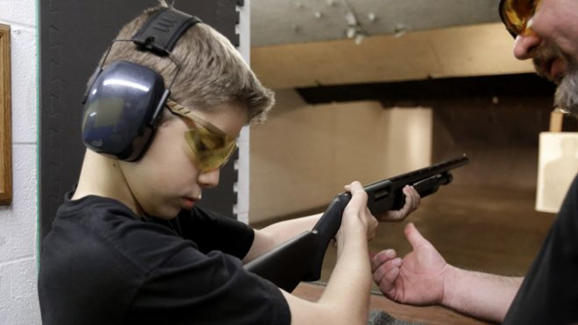 In this photo, Dan Blackford, right, shows Rory Strain, 12, how to hold a shotgun at a shooting range in Houston.