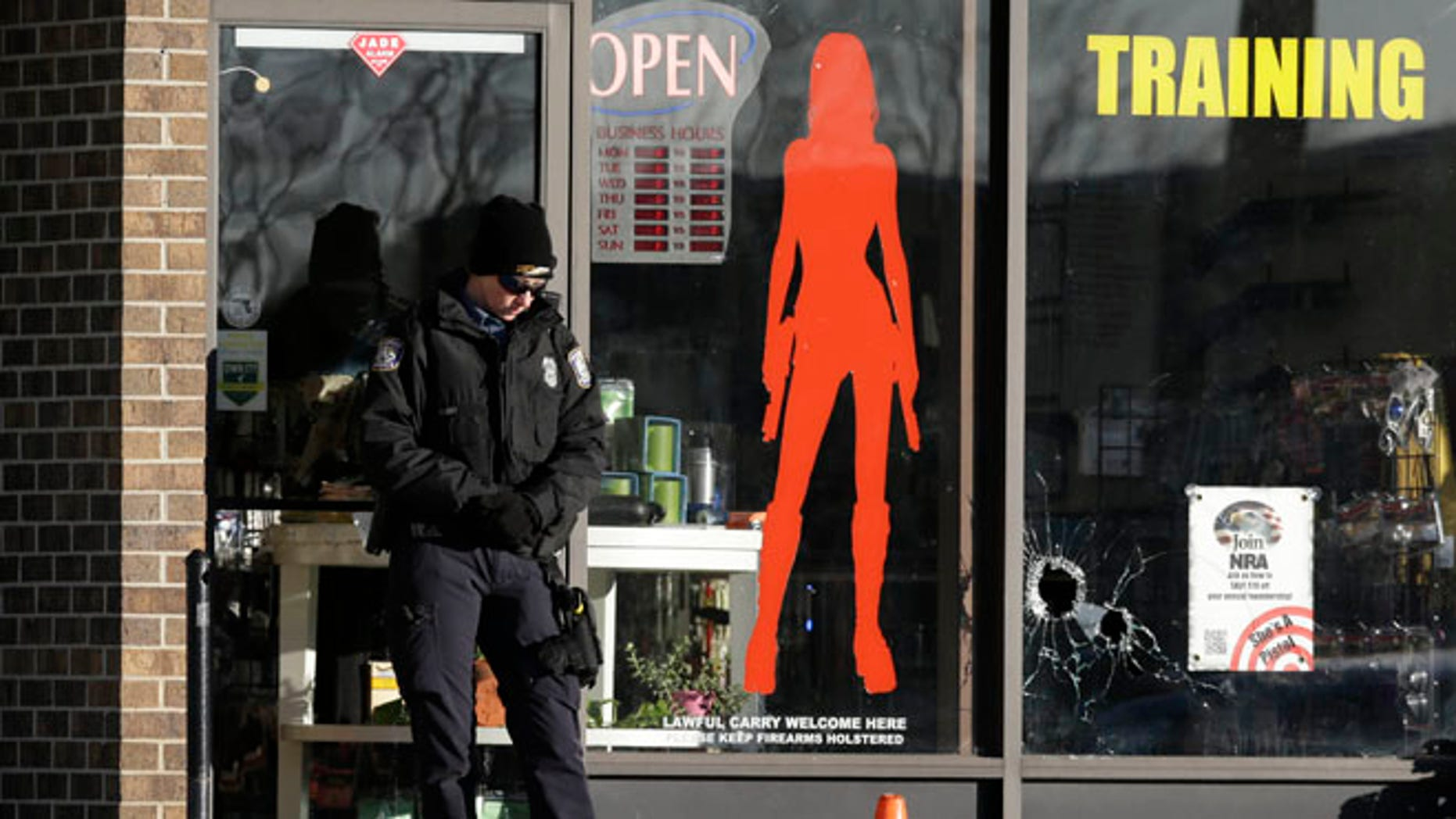 Jan. 9, 2015: A Law enforcement officer guards the scene of a shooting at She's a Pistol, LLC, a gun shop in Shawnee, Kan. (AP)