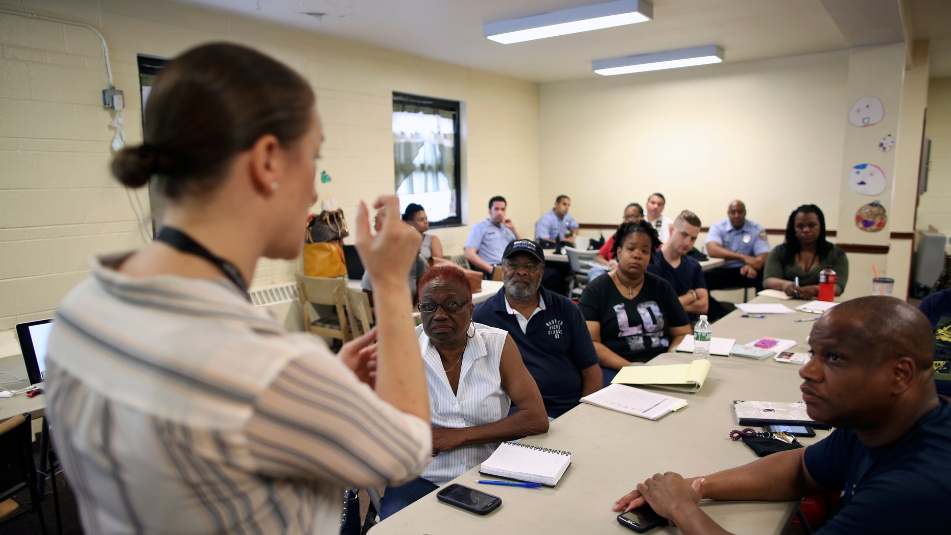 In this Saturday, July 9, 2016 photo, Dr. Zoe Maher, a Temple trauma surgeon, explains the Philadelphia Immediate Transport in Penetrating Trauma Trial (PIPT) to community leaders, at the Hunting Park Community Center, in Philadelphia. The difference between being a gunshot survivor or a homicide victim may be what happens in the ambulance. Several Philadelphia hospitals are coming together for a study that will ask: When gunshot victims are rushed to the emergency room, could paramedics do more to save them by doing less? (AP Photo/ Joseph Kaczmarek)