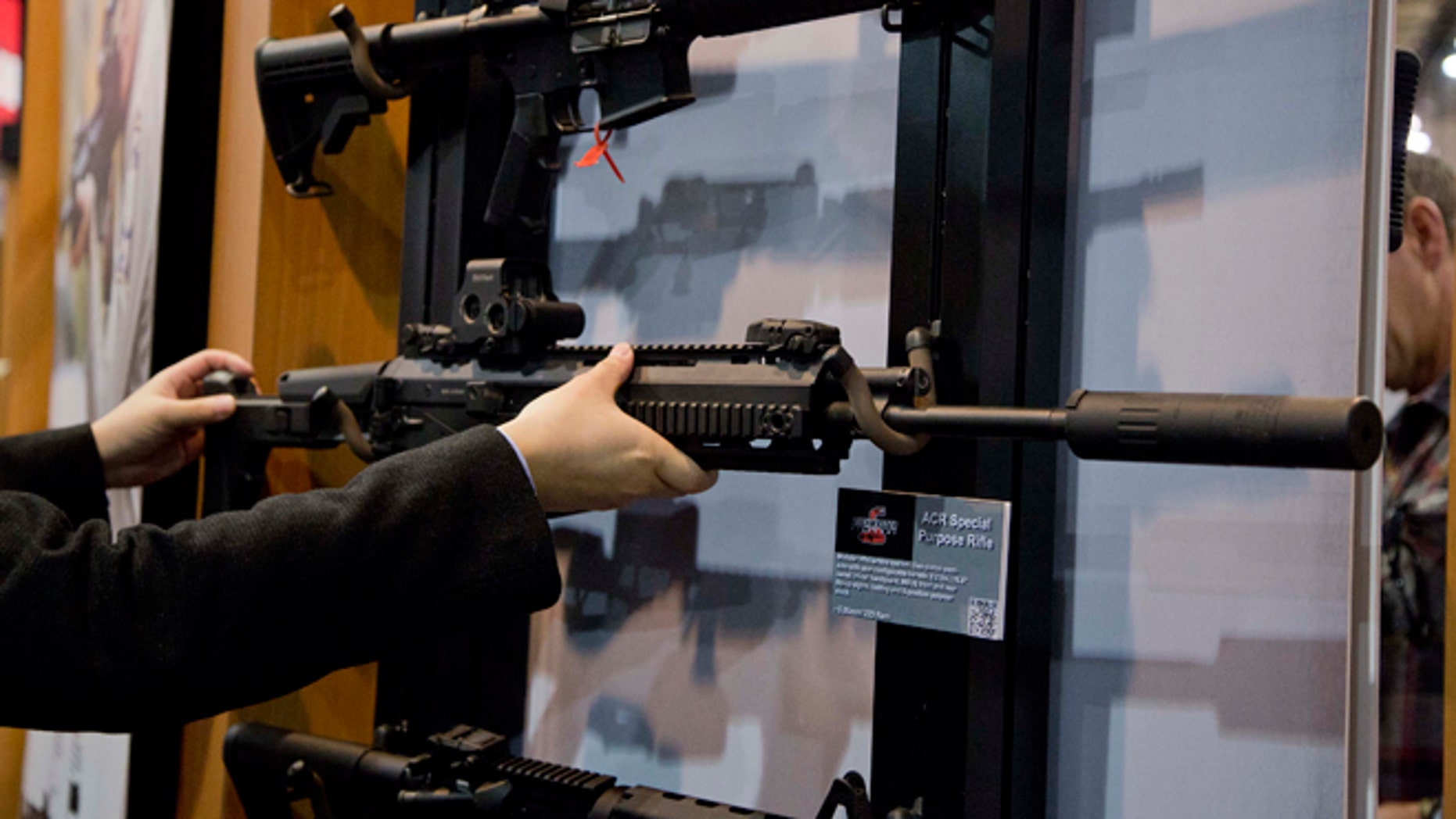 Jan. 15, 2013: Accessories manufacturer Kevin Kao, of Irvine, Calif., examines a military grade Remington ACR Special Purpose Rifle at the 35th annual SHOT Show in Las Vegas.