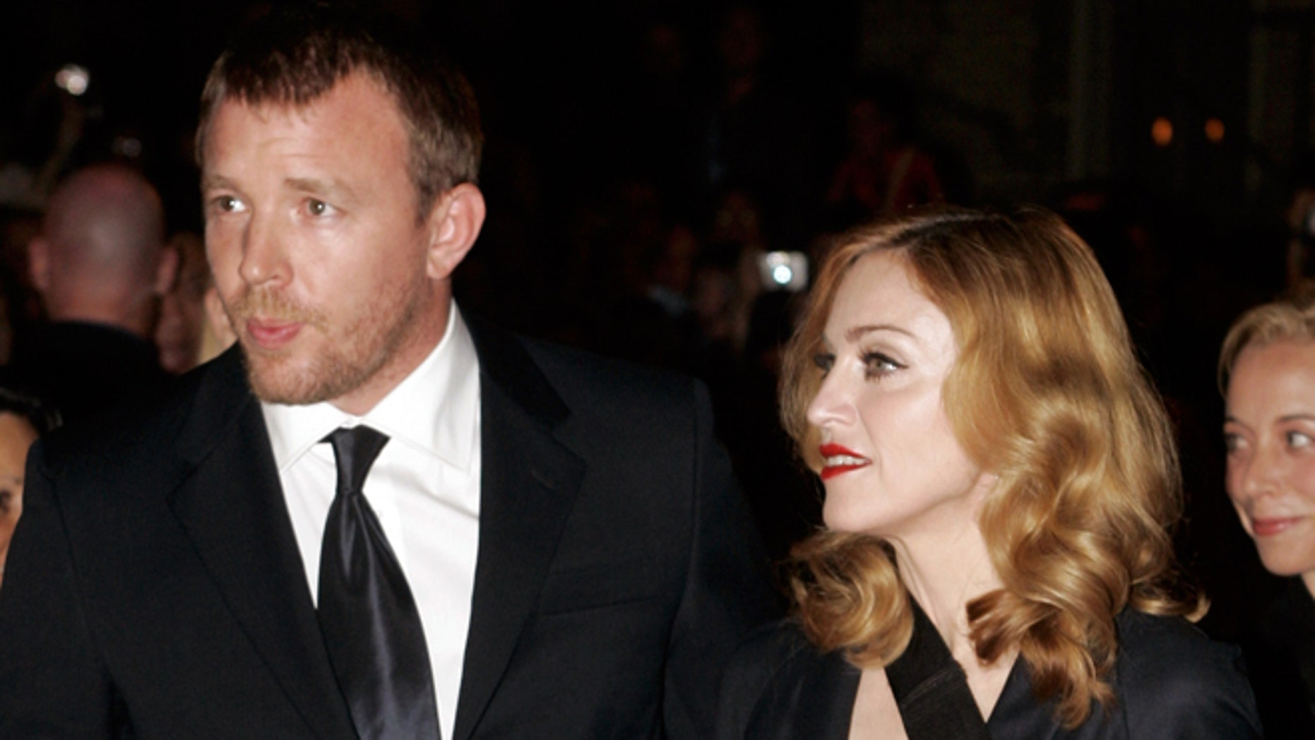 """September 11, 2005. Madonna (R) arrives with her husband, director Guy Ritchie, for the world premiere of Ritchie's film """"Revolver"""" in Toronto."""