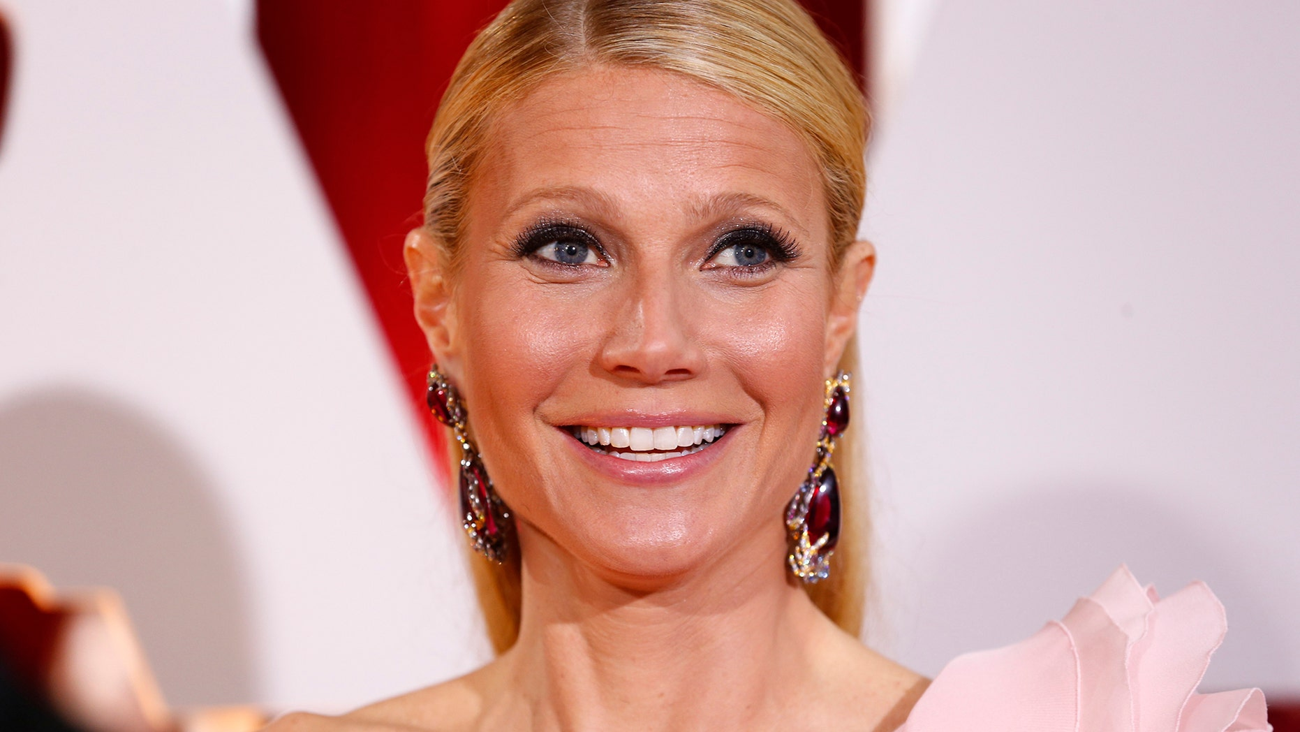 Actress Gwyneth Paltrow, wearing a custom Ralph & Russo pink one sleeve gown with a giant flower on the shoulder, arrives at the 87th Academy Awards in Hollywood, California February 22, 2015.