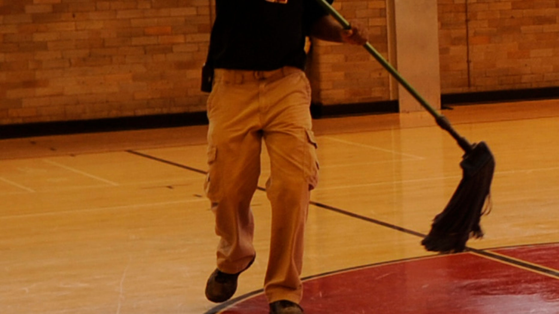 Lafayette Rockette, facility manager at East High School, cleans the floor, Monday, November 06, 2011, in the Calloway Gym at East High School that was built in 1924. RJ Sangosti, The Denver Post