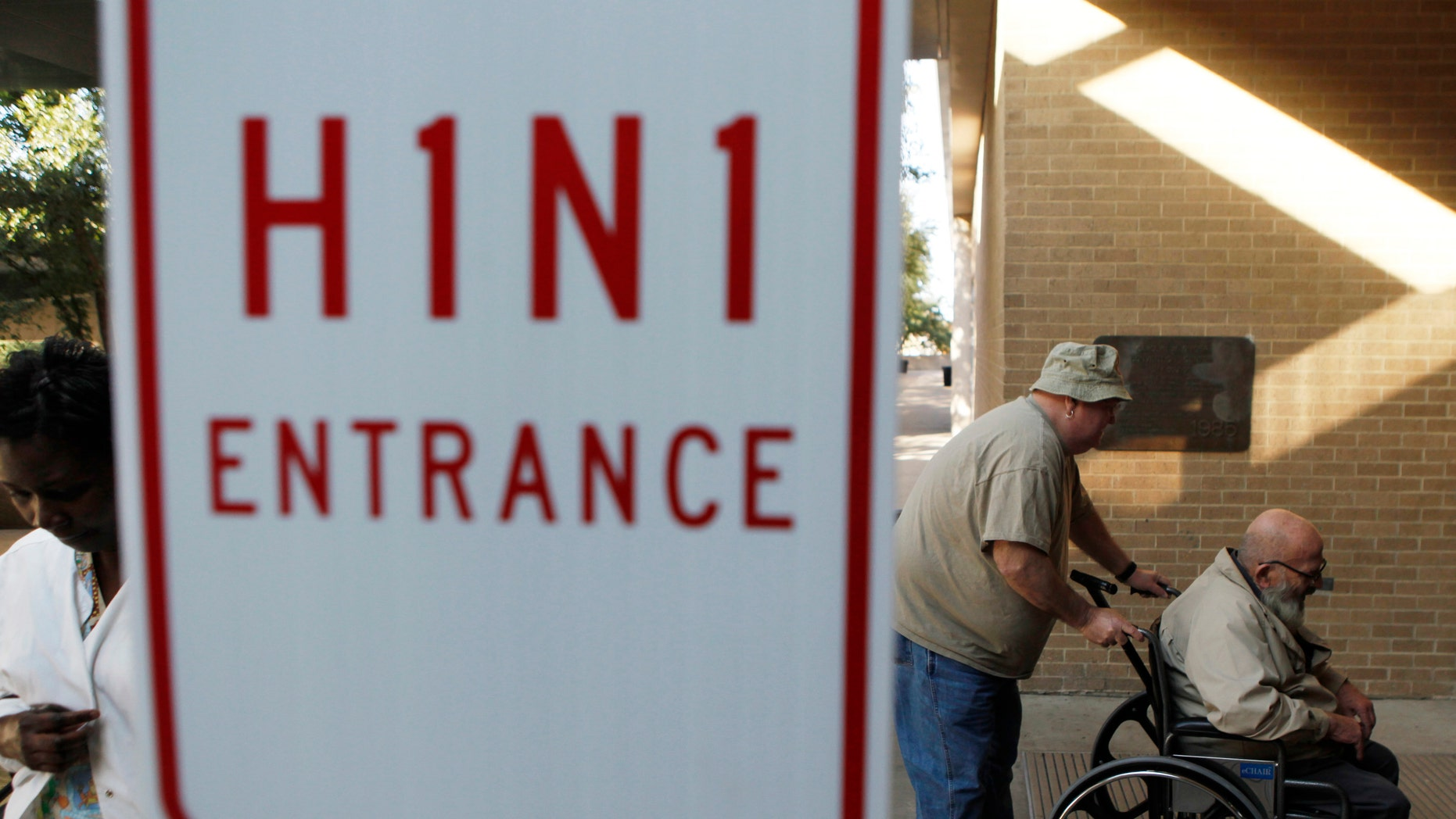 Men enter the Arlington Convention Center to receive their H1N1 flu vaccinations in Arlington, Texas November 24, 2009. (REUTERS/Jessica Rinaldi)