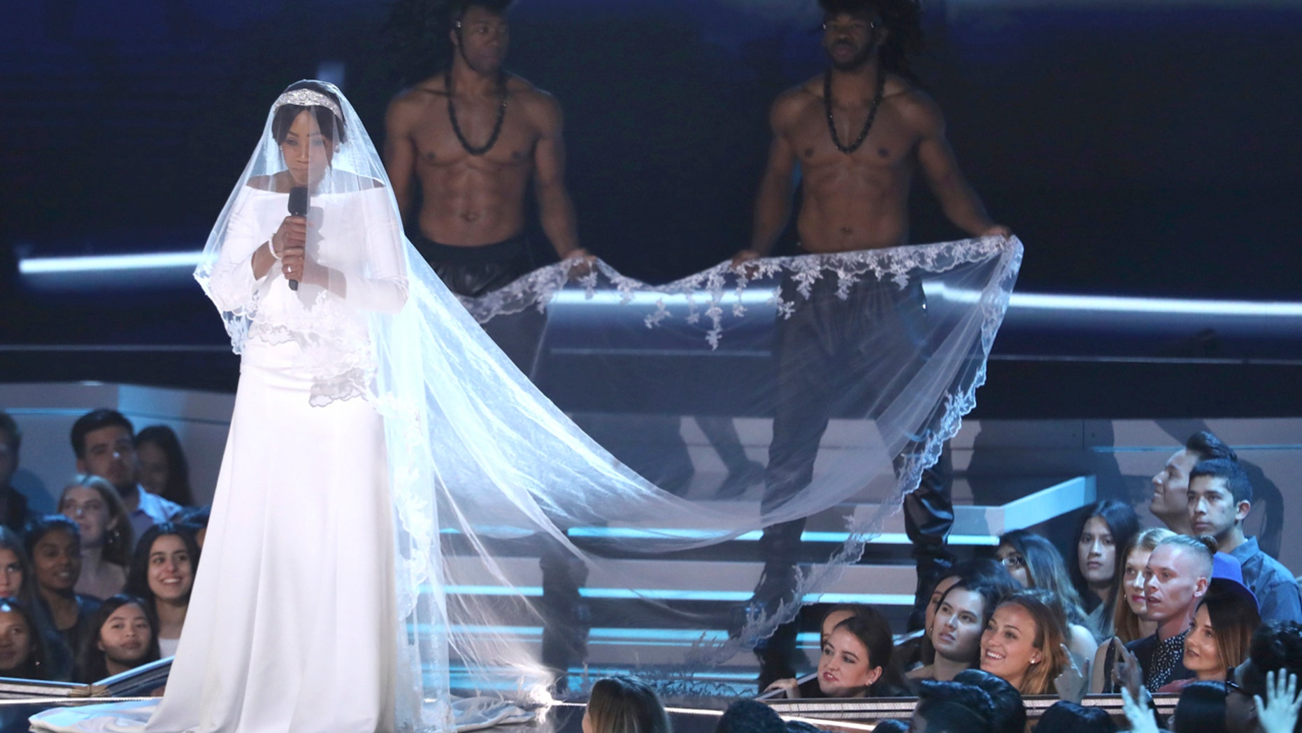 Tiffany Haddish appears on stage at the MTV Movie and TV Awards wearing a full on replica of Meghan Markle's royal wedding gown.