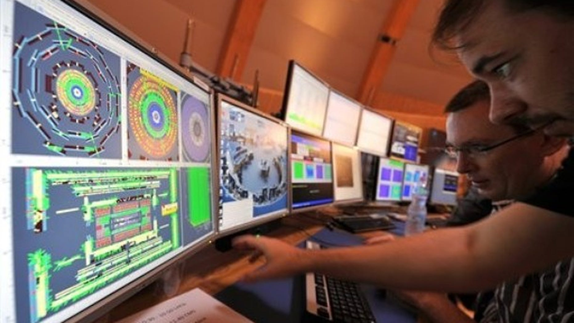 European Center for Nuclear Research (CERN) scientists control computer screens showing traces on Atlas experiment of the first protons injected in the Large Hadron Collider (LHC) during its switch on operation in CERN's control room, near Geneva, Switzerland.