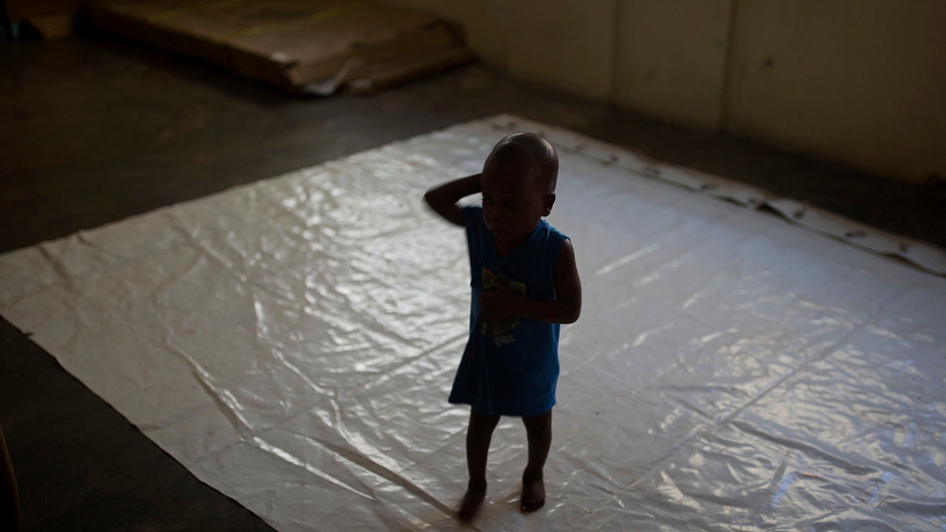 A boy stands on a tarp at the Foyer Notre Dame de la Nativite orphanage on