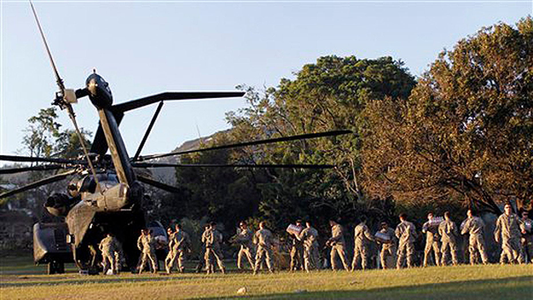 Monday: U.S. troops with the 82nd Airborne Division unload disaster relief supplies in Port-au-Prince. Troops, doctors and aid workers flowed into Haiti on Monday even while hundreds of thousands of Tuesday's quake victims struggled to find water or food. (AP Photo)