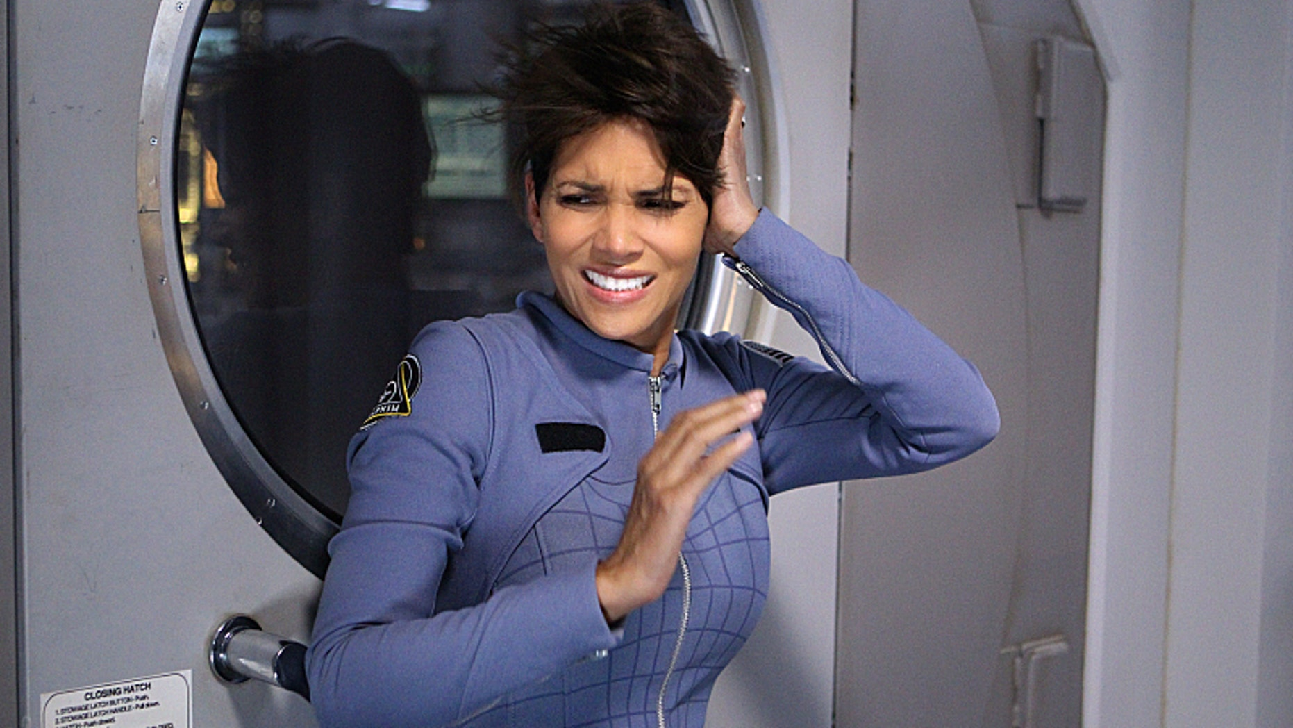 """This image released by CBS shows Halle Berry in a scene from the series """"Extant."""" Berry plays an astronaut who returns home from a yearlong solo mission only to discover that, while in flight, she was somehow impregnated."""