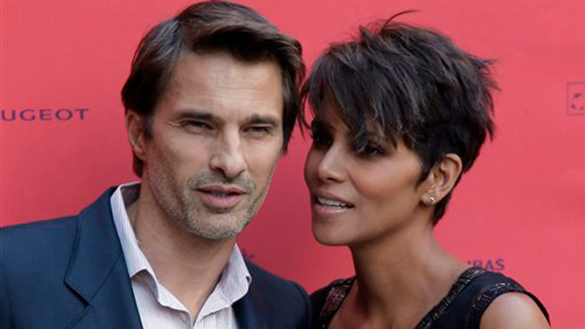 """FILE - In this June 13, 2013 file photo, actor and president of the Champs-Elysees Film Festival Olivier Martinez, left, poses with Actress Halle Berry prior to the screening of the film """"Things We Lost in the Fire"""" with the french title """"Nos Souvenirs Brules"""" during the Champs-Elysees Film Festival, at the """"Publicis Cinema"""" in Paris. Berry and Martinez are ending their two-year marriage. The couple released a joint statement Tuesday, Oct. 27, 2015, saying they plan to divorce. (AP Photo/Francois Mori, File)"""