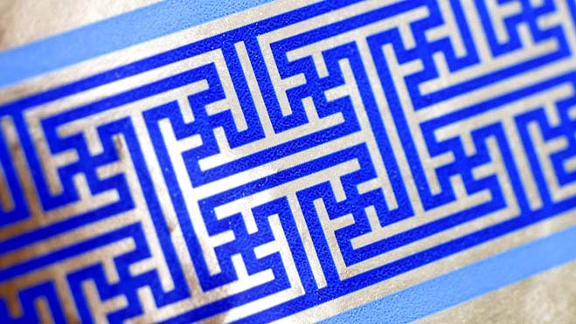 Dec. 8, 2014: Cheryl Shapiro displays the Hanukkah gift wrap with a swastika-like pattern she found at Walgreens in Northridge, Calif.  The wrapping paper has been recalled from stores nationwide.