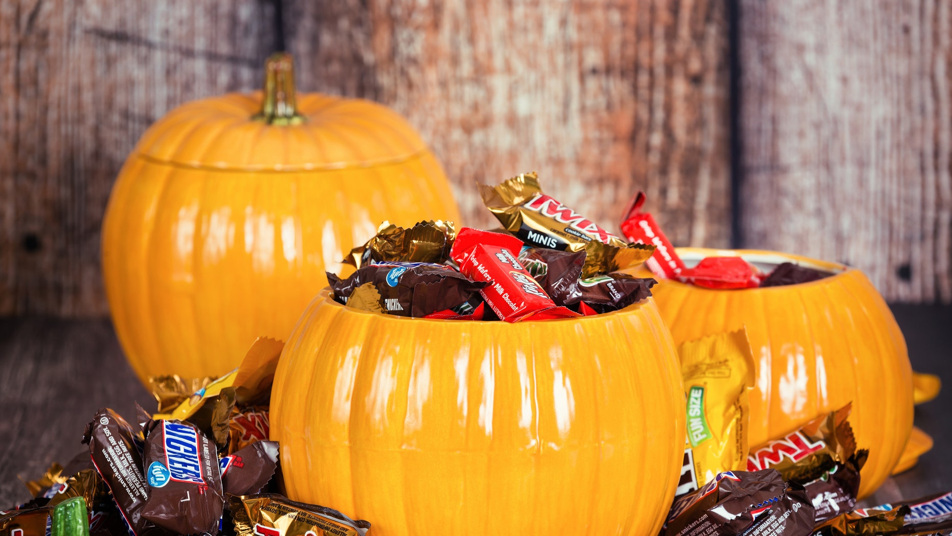 Dallas, United States - October 31, 2015: Decorative pumpkins filled with assorted Halloween chocolate candy made by Mars, Incorporated and the Hershey Company.