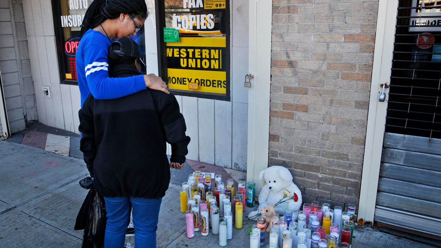 Anysia Manderson, left, comforts Amina Harris as they look at a makeshift memorial for those killed during a shooting at a Halloween party in Newburgh, N.Y., Monday, Oct. 31, 2016. Two were killed and several others injured in the weekend shooting. (AP Photo/Seth Wenig)