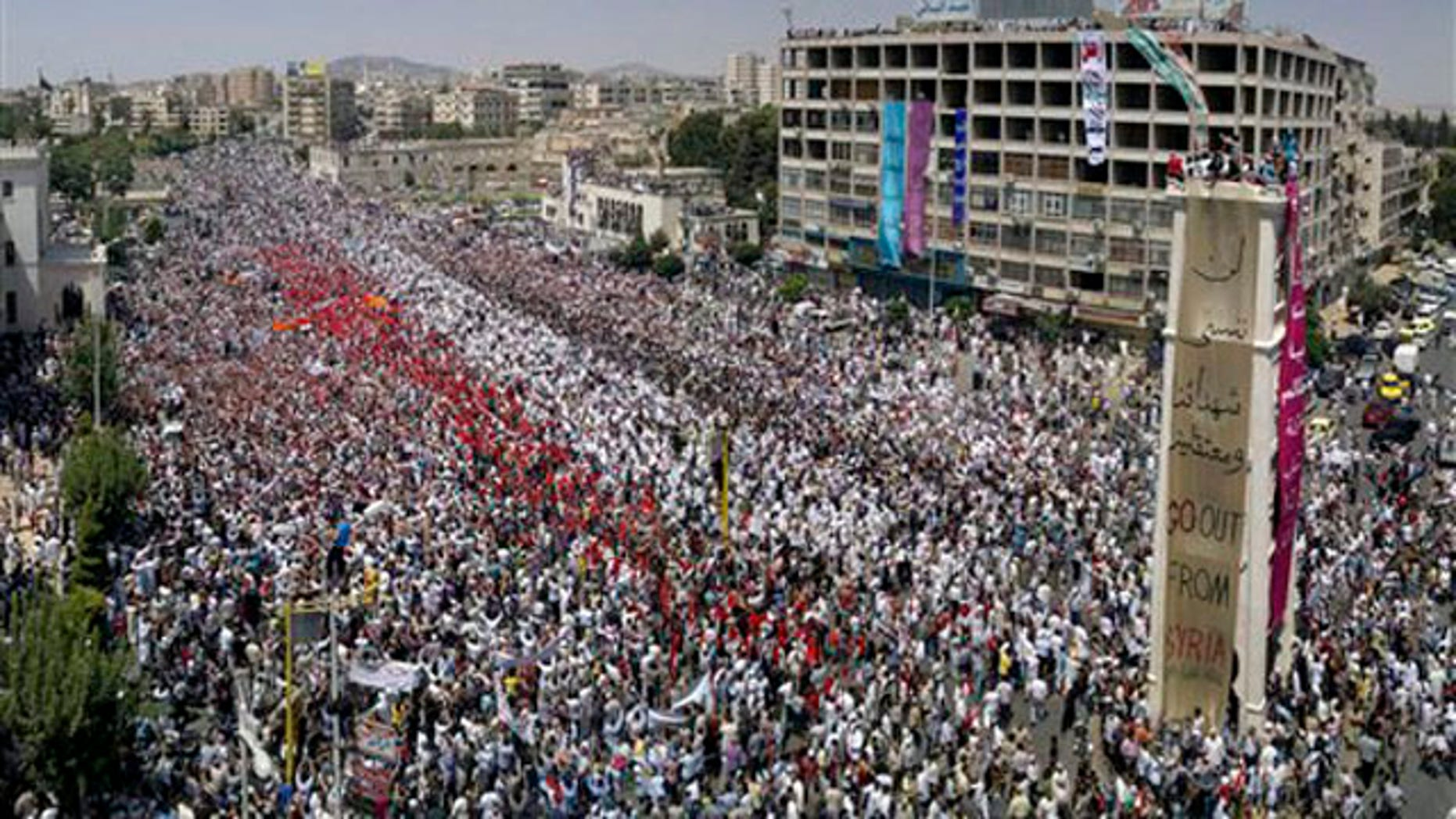 A citizen journalism image made July 22 on a mobile phone and provided by Shaam News Network shows Syrian anti-regime protesters gather during a rally in al-Assy square in the western city of Hama, Syria.