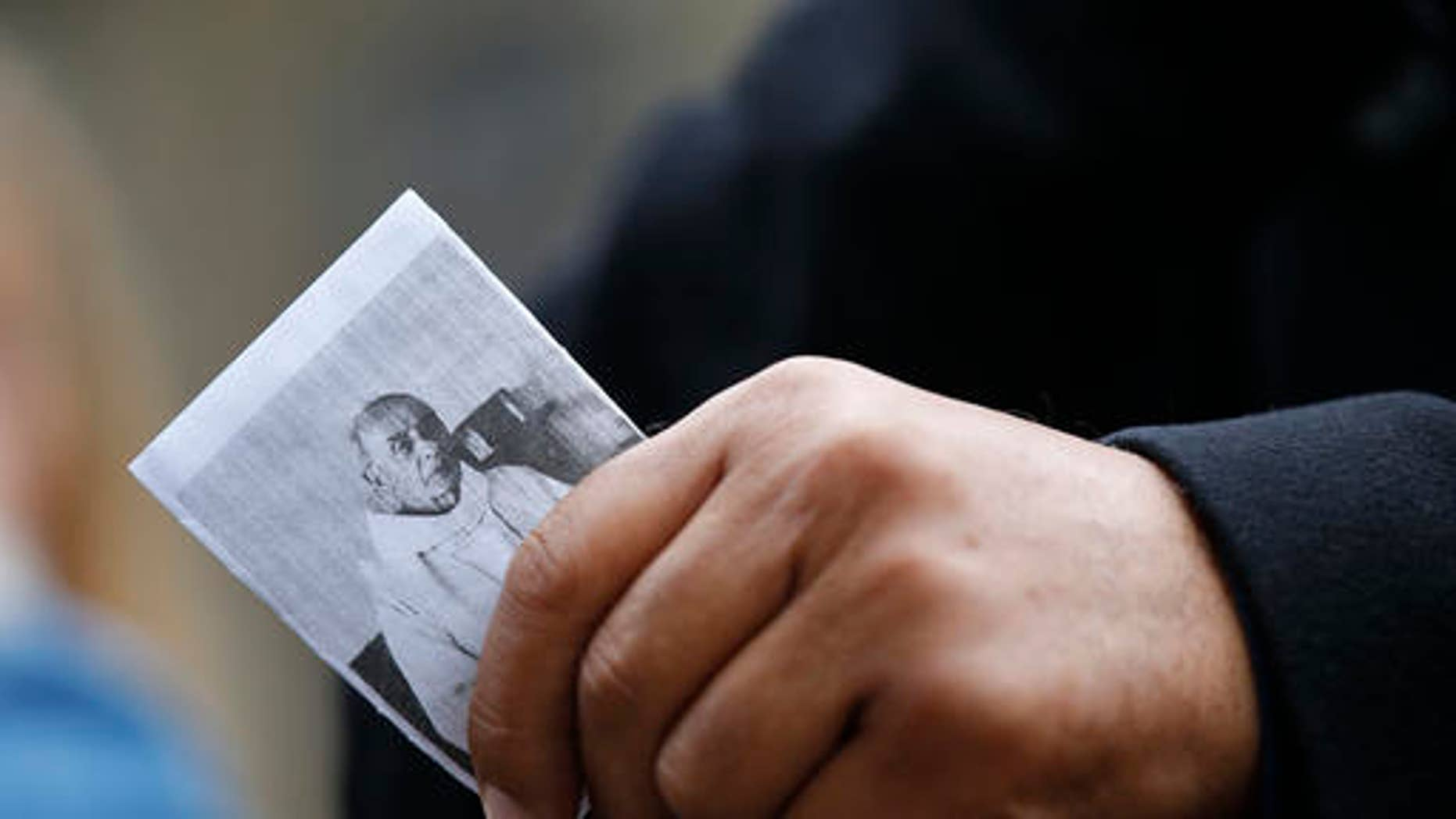 A man holds a religious leaflet showing the priest Jacques Hamel during his funeral mass, outside the Rouen cathedral, Normandy, Tuesday, Aug.2, 2016. Father Jacques Hamel, 85, was killed by two ISIS extremists as he celebrated morning Mass.