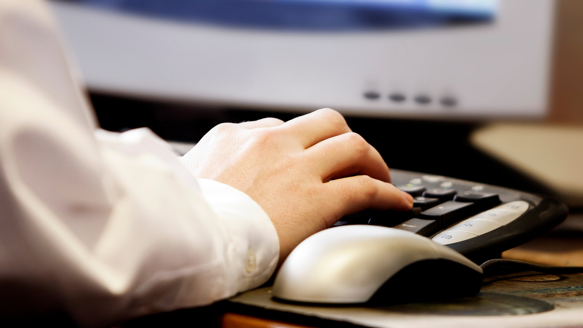 Close-up of a man's hand typing on a computer keyboard, with monitor and mouse (shallow focus).