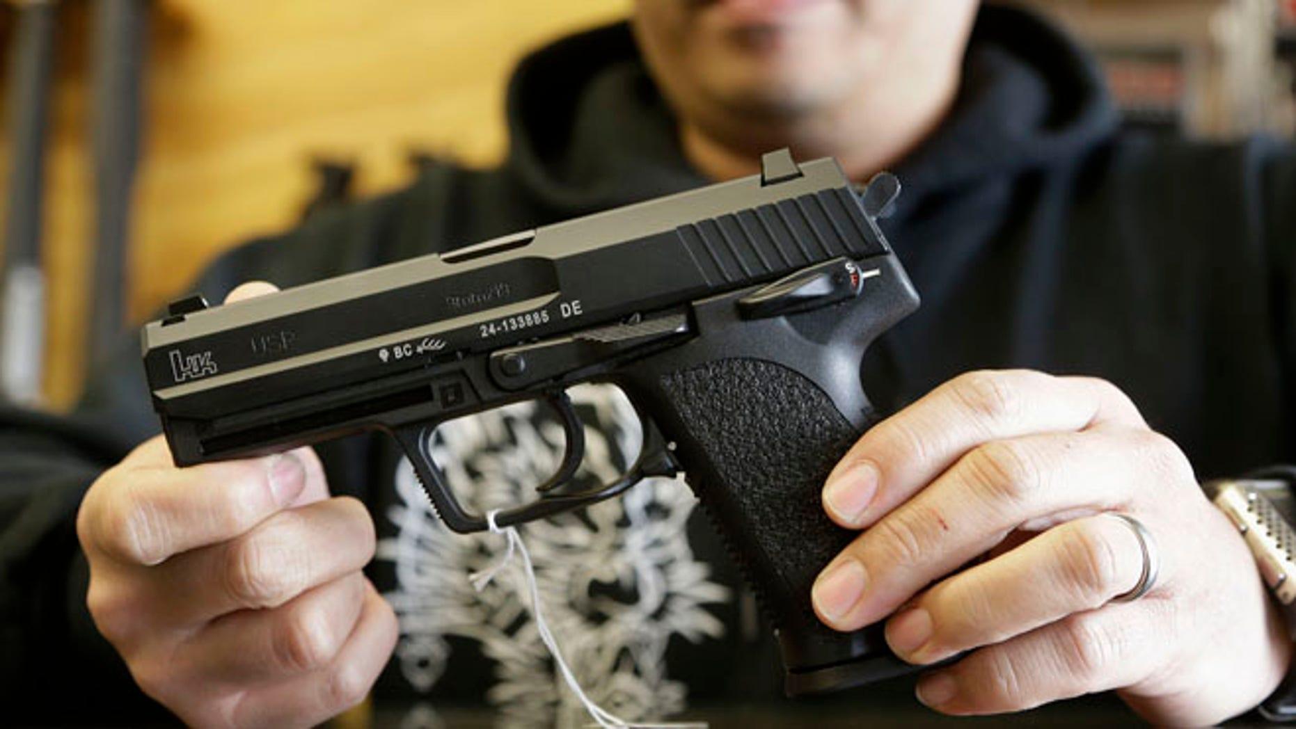 Dec. 19, 2012: A gun store worker holds up an HK USP 9mm handgun at High Bridge Arms Inc. in San Francisco.
