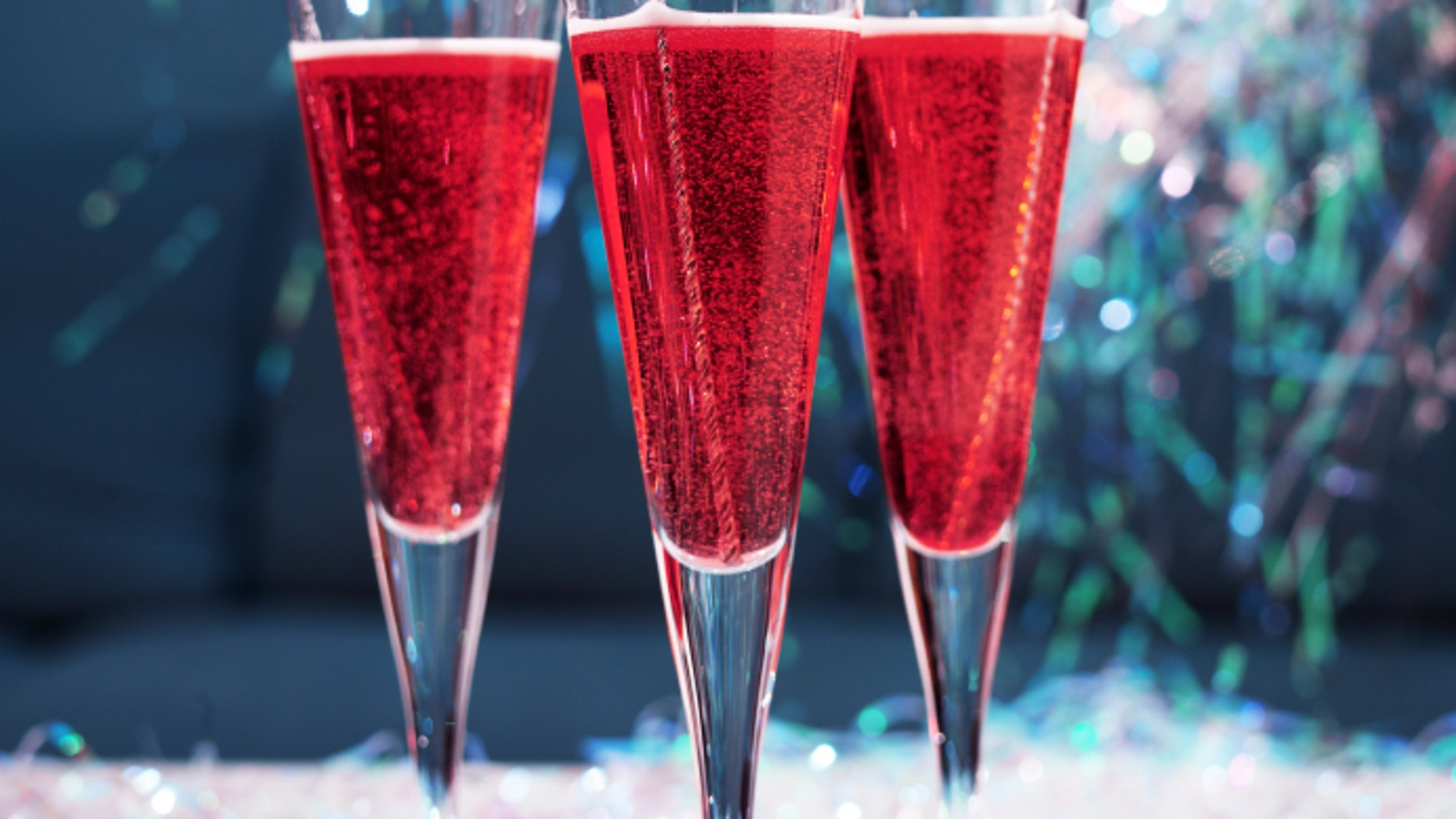 Champagne cocktails with tinsel and glitter in a festive party setting.f