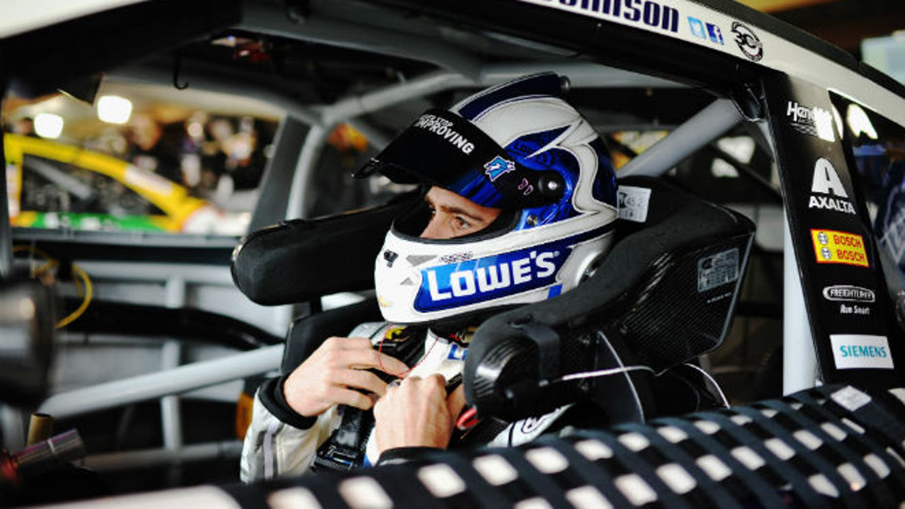 Jimmie Johnson, six-time NASCAR Sprint Cup Series champion and driver of the #48 Lowe's Chevrolet, sits in his car during practice for the NASCAR Sprint Cup Series STP 500 at Martinsville Speedway on March 28, 2014 in Martinsville, Virginia. The HANS device is the collar attached to the helmet via tether; it is also secured to the shoulder harness and seat. (Photo by Rainier Ehrhardt/NASCAR via Getty Images)