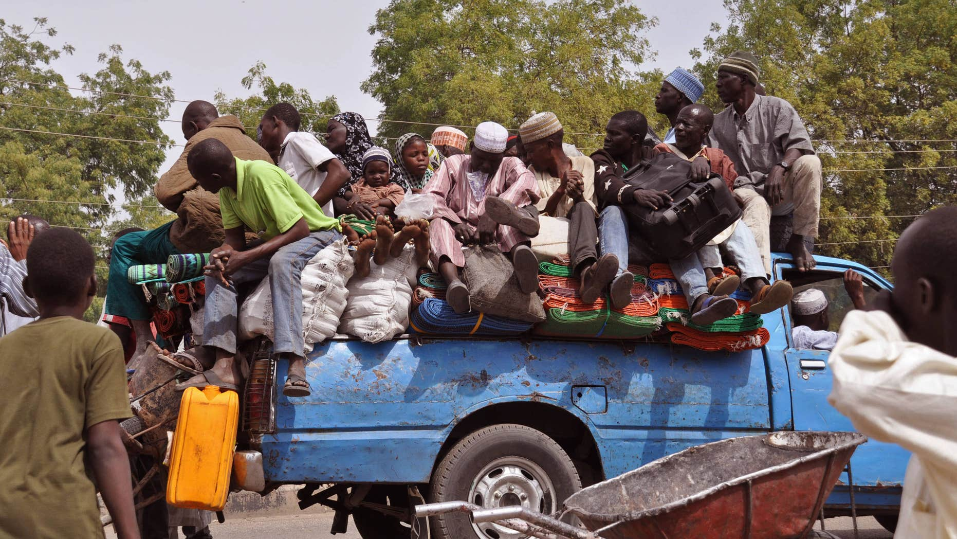 Jan. 27, 2015: villagers sit on the back of a small truck as they and others flee the recent violence near the city of Maiduguri, Nigeria.