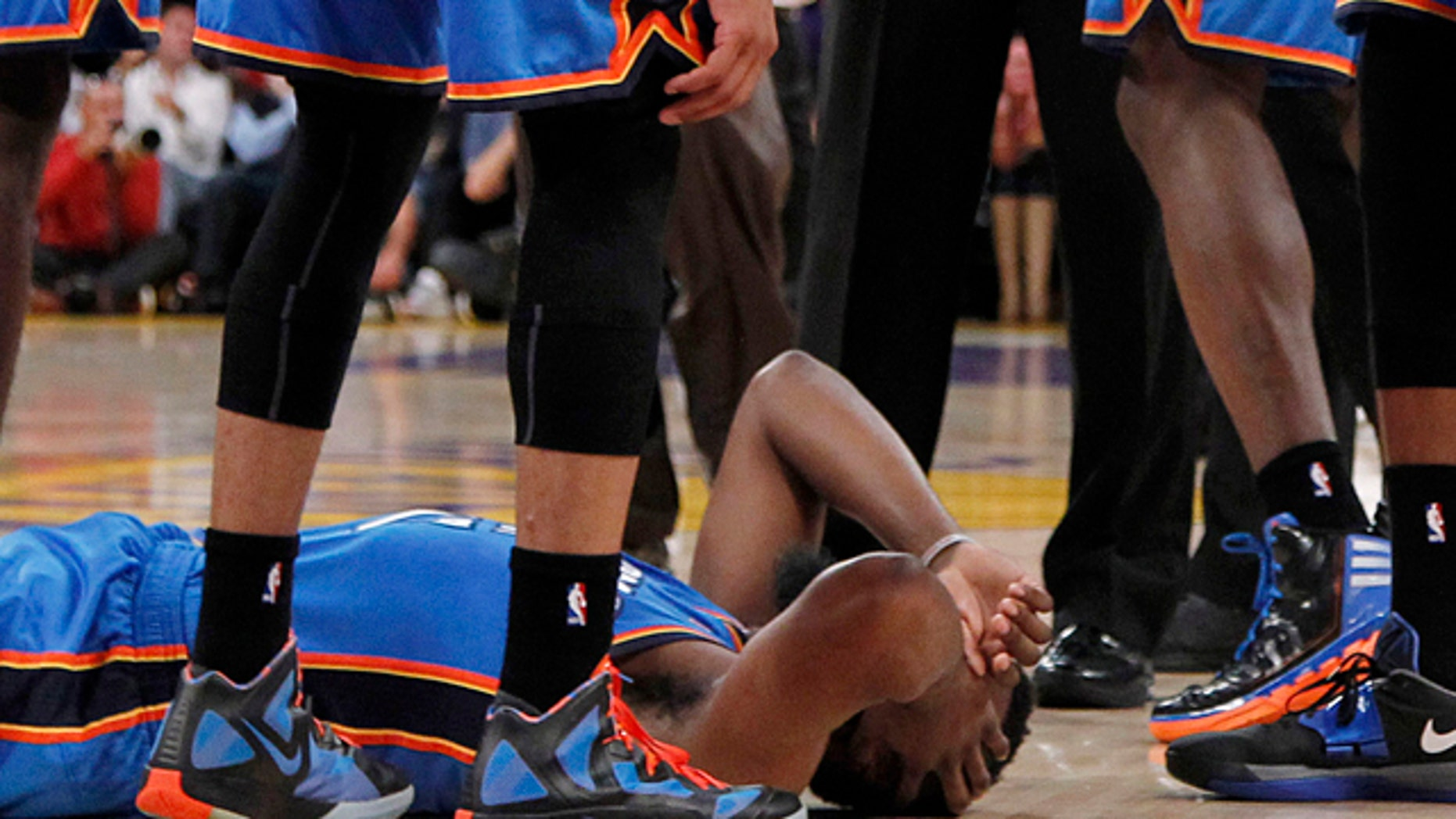 April 22, 2012: Oklahoma City Thunder players stand over teammate James Harden, lower left, after receiving a flagrant double foul from Los Angeles Lakers' Metta World Peace, who was then ejected, in the first half of an NBA basketball game in Los Angeles. (AP)