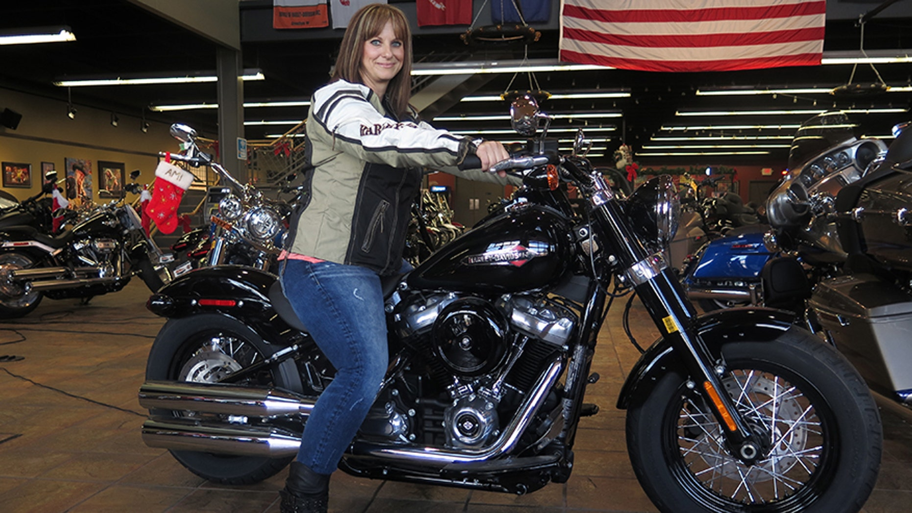 """In this Dec. 12, 2017, photo, Terri Meehan poses on a 2018 Harley Softail Slim in Milwaukee's House of Harley. Meehan took a riding course at the dealership as part of Harley-Davidson's """"Riding Academy,"""" an initiative the company hopes will help bring new customers. (AP Photo/Ivan Moreno)"""