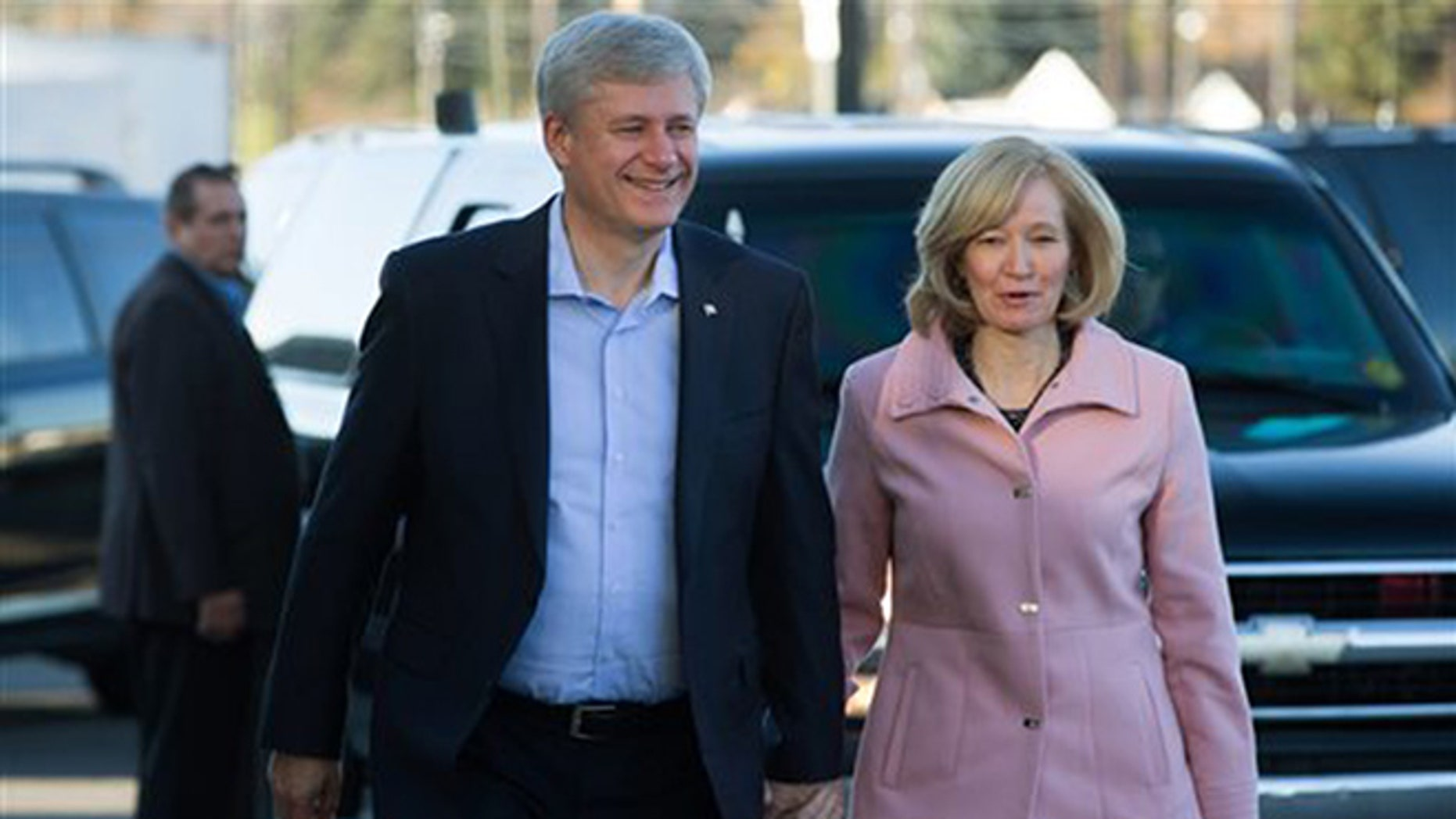 Conservative Leader, Prime Minister Stephen Harper, left, and his wife Laureen arrive to cast their ballots in the federal election in Calgary, Alberta, on Monday, Oct. 19, 2015. Canadians voted Monday to decide whether to extend Harper's near-decade in power or return Canada to its more liberal roots. (Darryl Dyck/The Canadian Press via AP) MANDATORY CREDIT