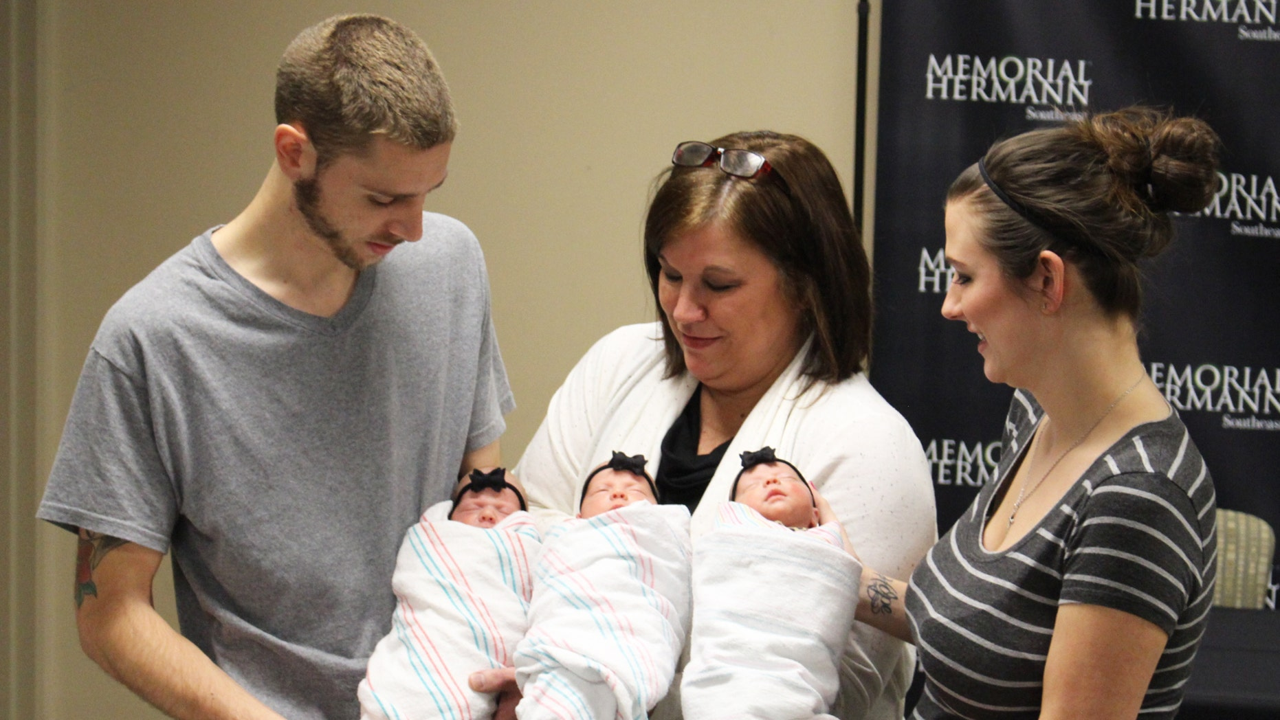 Proud Parents Brad and Stephanie Harris and grandmother Lynn Sweat holding (from left to right) identical triplets Savannah, Addison and Kinsley Harris.