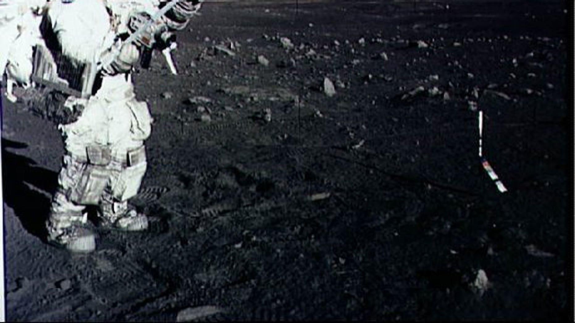 Astronaut Harrison Schmitt collects lunar rake samples during an Apollo 17 moonwalk in December 1973.