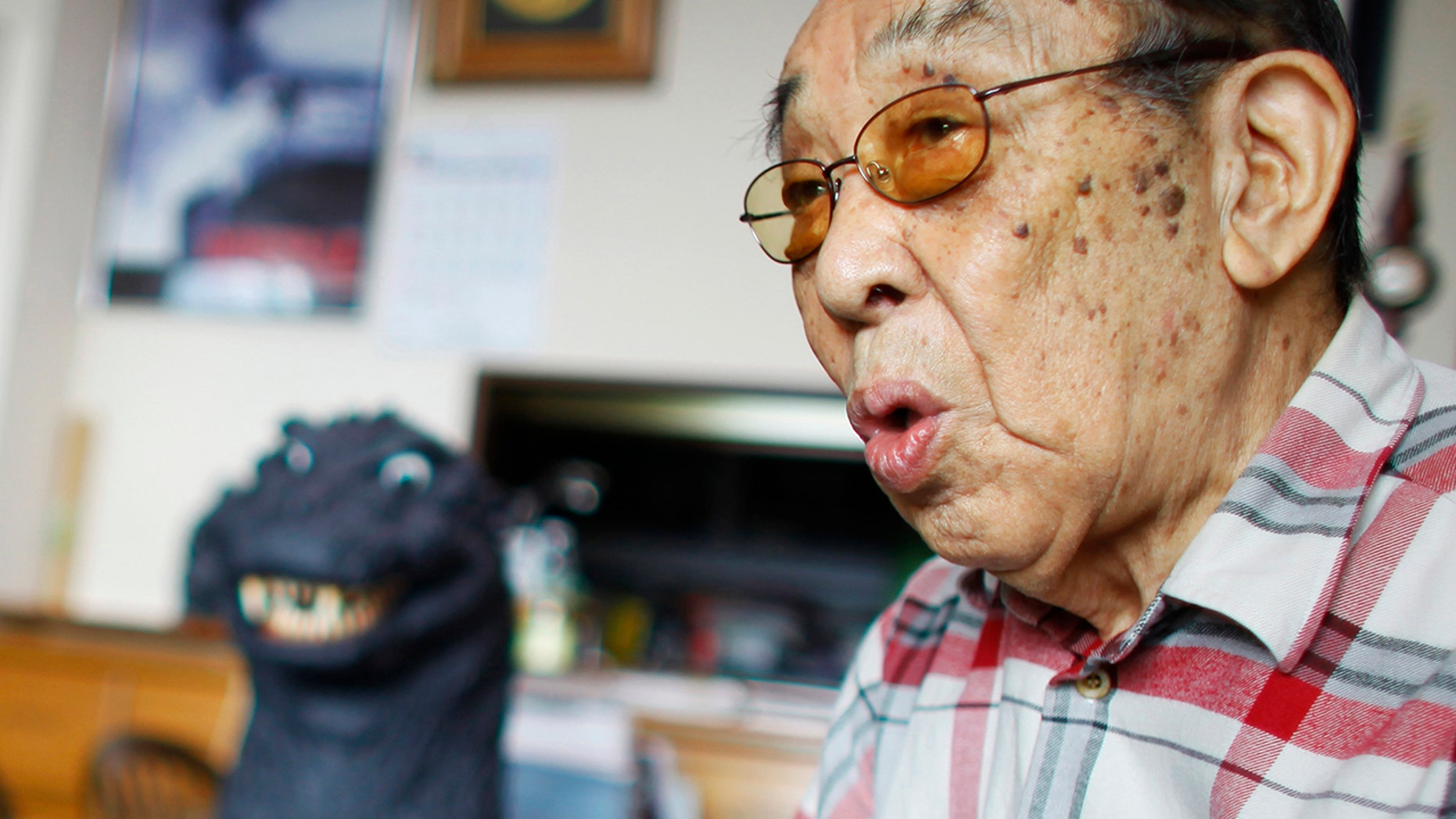 In this April 28, 2014 photo, original Godzilla suit actor Haruo Nakajima, who has played his role as the monster, speaks during an interview at his home in Sagamihara, near Tokyo. Nakajima, the actor who stomped in a rubber suit to portray the original 1954 Godzilla, has died on Monday, Aug. 7, 2017.