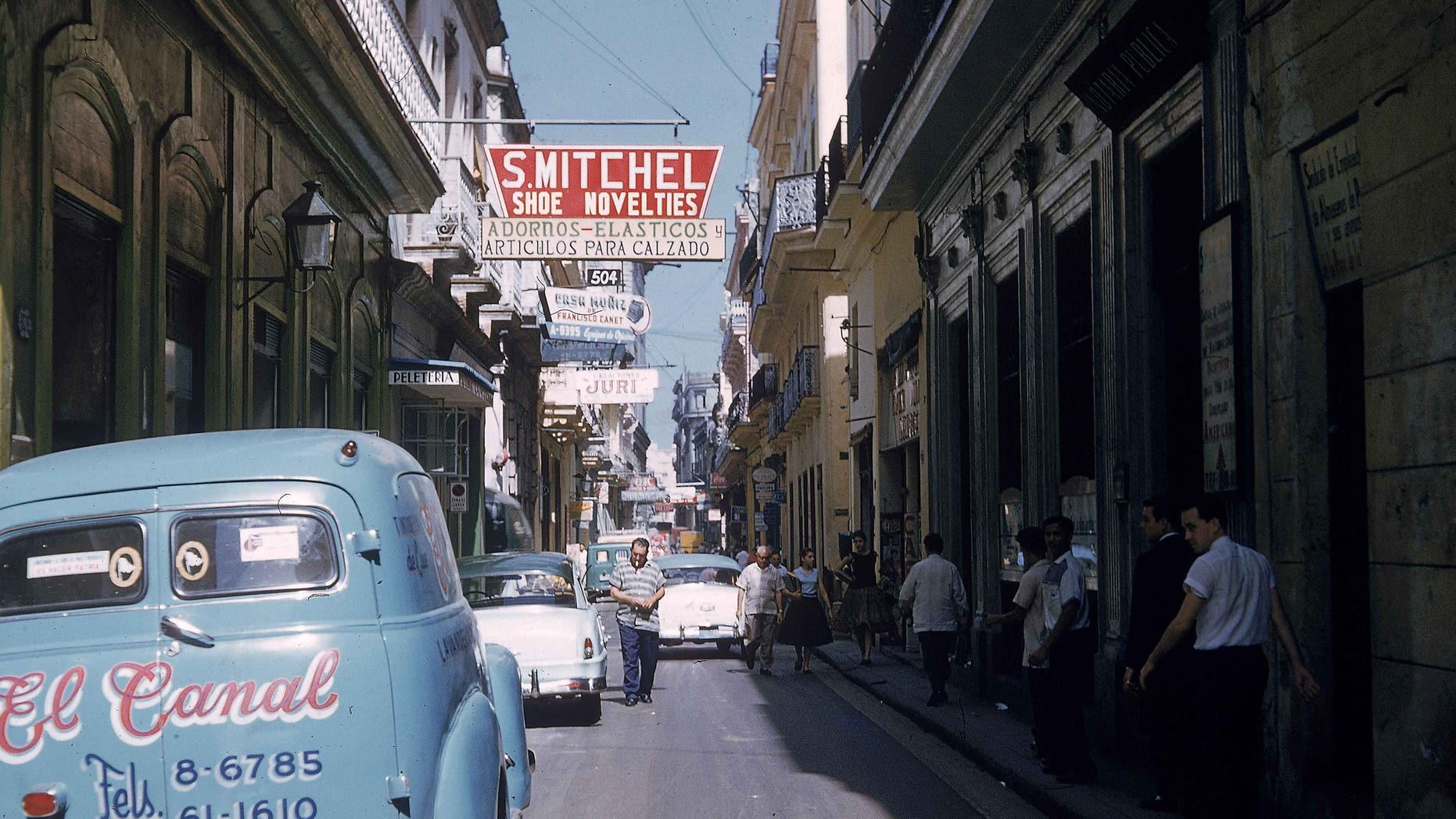 Cars are parked along a narrow street as pedestrians walk in the shade in Havana, Cuba, 1950s.