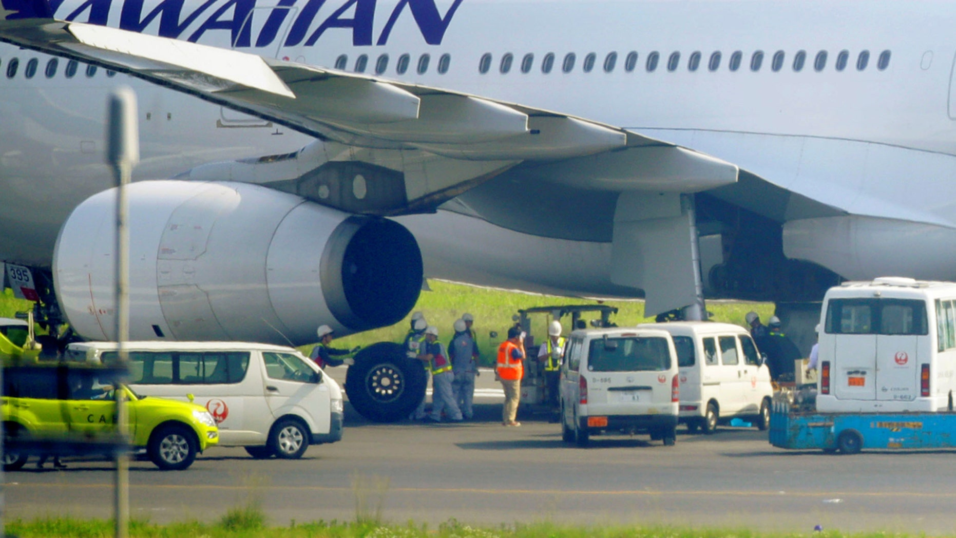 Officials change a tyre of a Hawaiian Airlines aircraft after making emergency landing at Haneda airport in Tokyo, Japan, in this photo taken by Kyodo July 18, 2016. (Reuters)