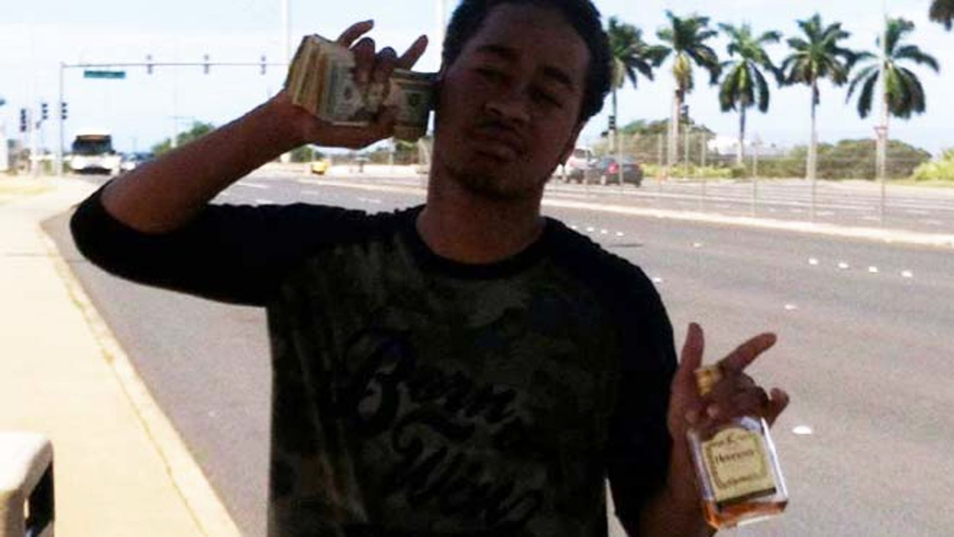 Kalani Watson aka Kiki Seui posts himself on his Facebook account with wads of cash two days after allegedly robbing a Reynolds Recycling center of $500. (HawaiiReporter.com)