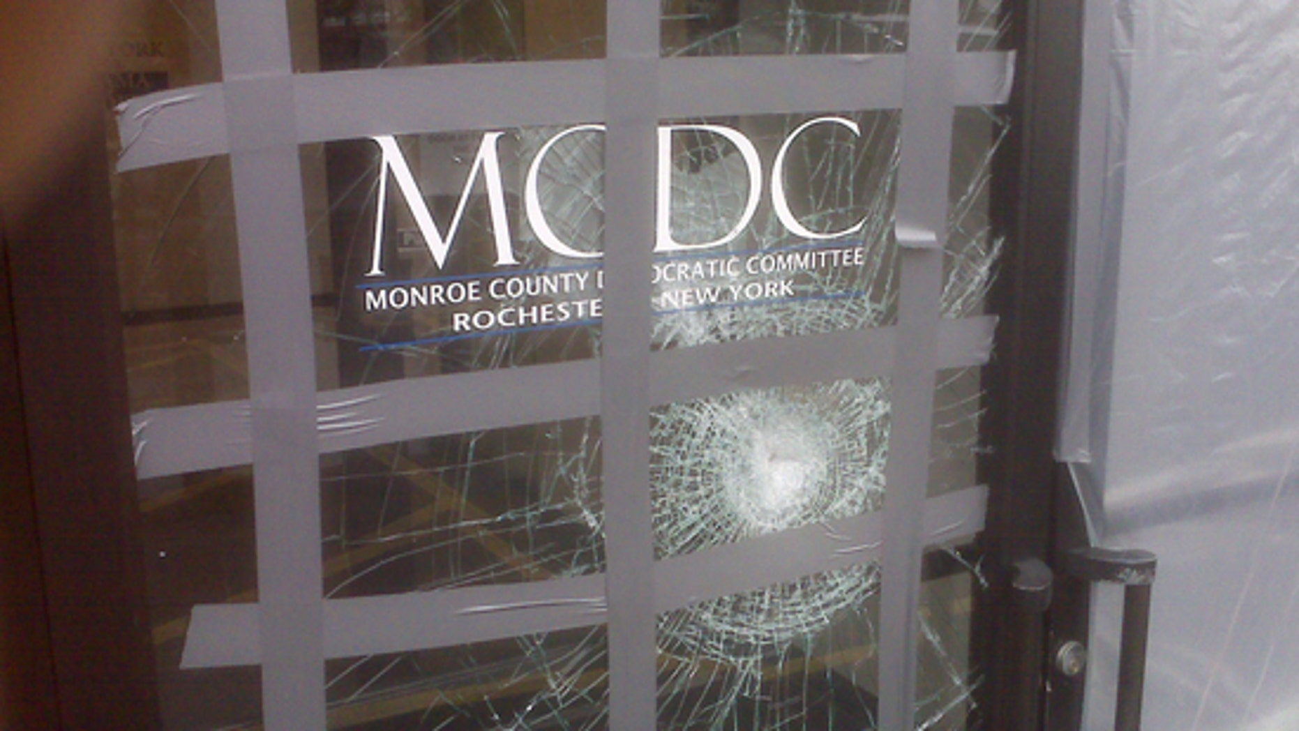 "This picture provided on Wednesday, March 24, 2010 by the Monroe County Democratic Committee in Rochester, N.Y. shows damage to their office after a glass door was struck with a brick with a note reading ""Exremism in Defense of Liberty Is no Vice"" sometime from late Saturday, March 20, 2010 or Sunday, March 21, 2010.(AP)"
