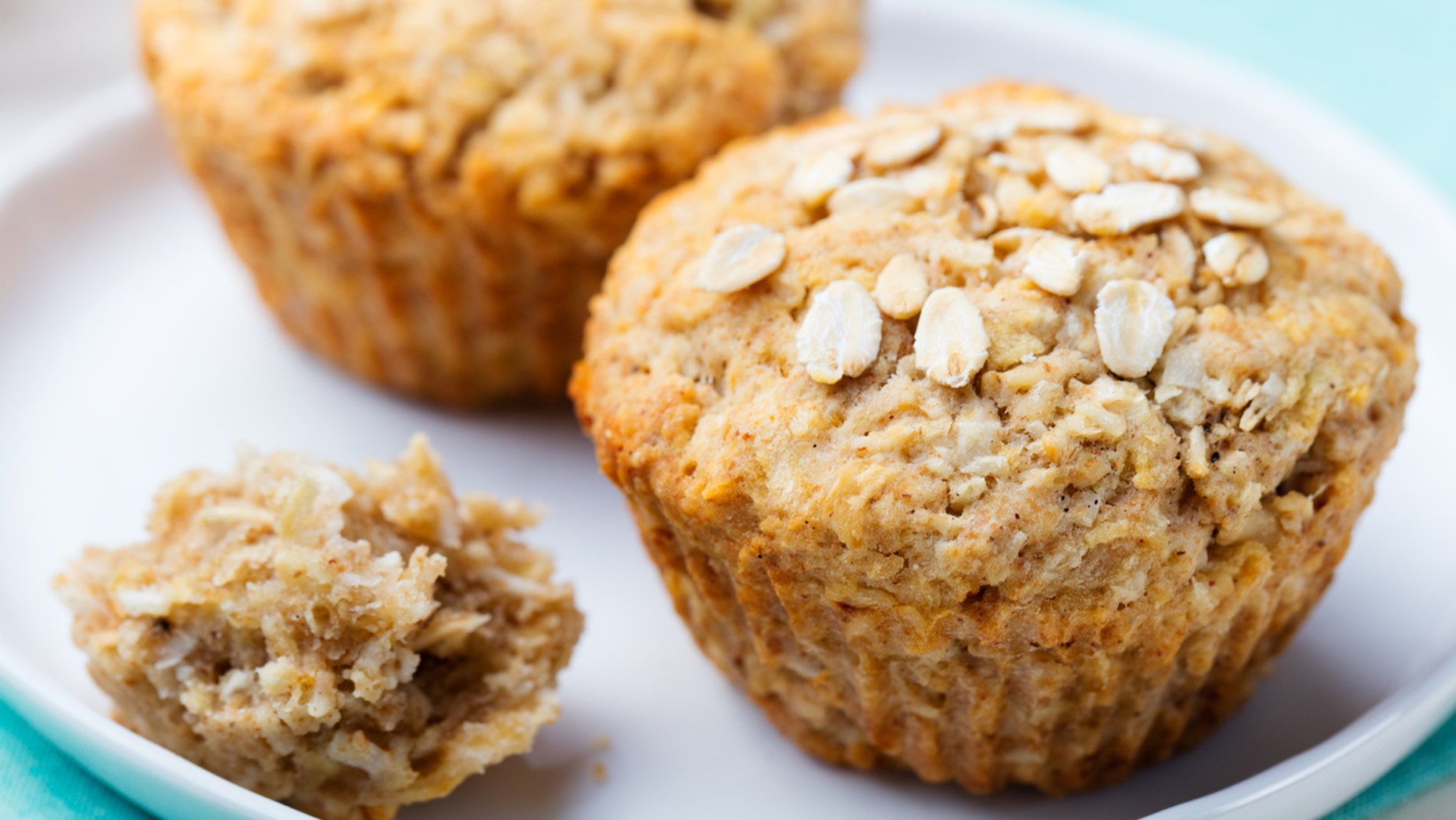 Healthy vegan oat muffins, apple and banana cakes with sour cream on a white plate Blue stone background