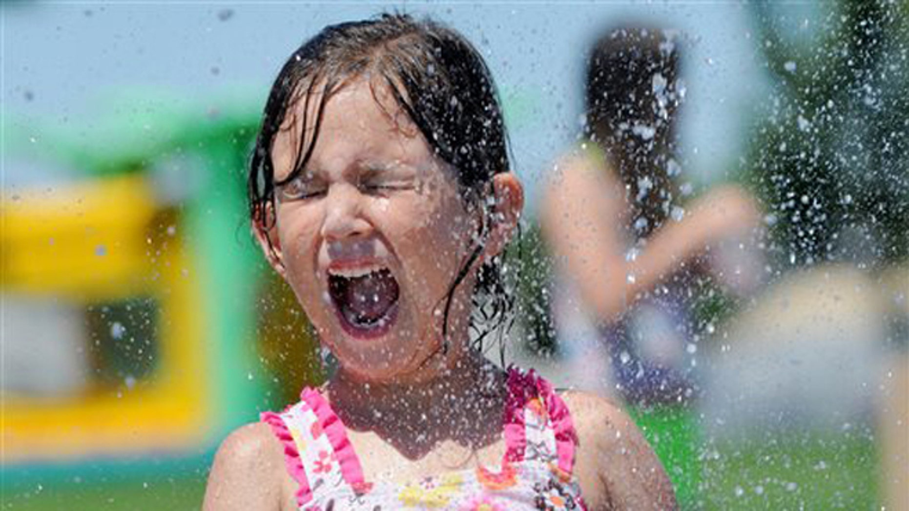 Kayla Holdridge, 6, of Eagle, is sprayed with water at Settlers Park Friday, June 28, 2013 in Meridian, Idaho. Many people looked for ways to beat the heat as temperatures in the Treasure Valley soared into the triple digits. (AP Photo/The Idaho Press-Tribune, Adam Eschbach)