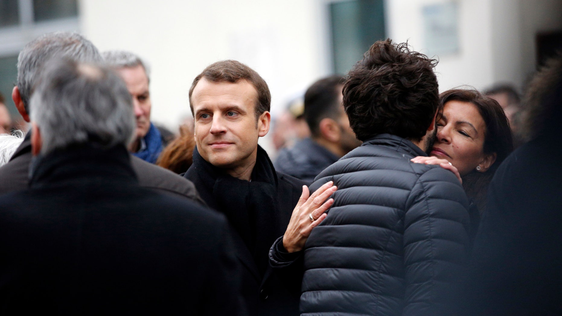 French President Emmanuel Macron, center and Paris mayor Anne Hidalgo speaks to relatives of victims outside the satirical newspaper Charlie Hebdo former office as they mark the third anniversary of the attack, in Paris, Sunday, Jan. 7, 2018.