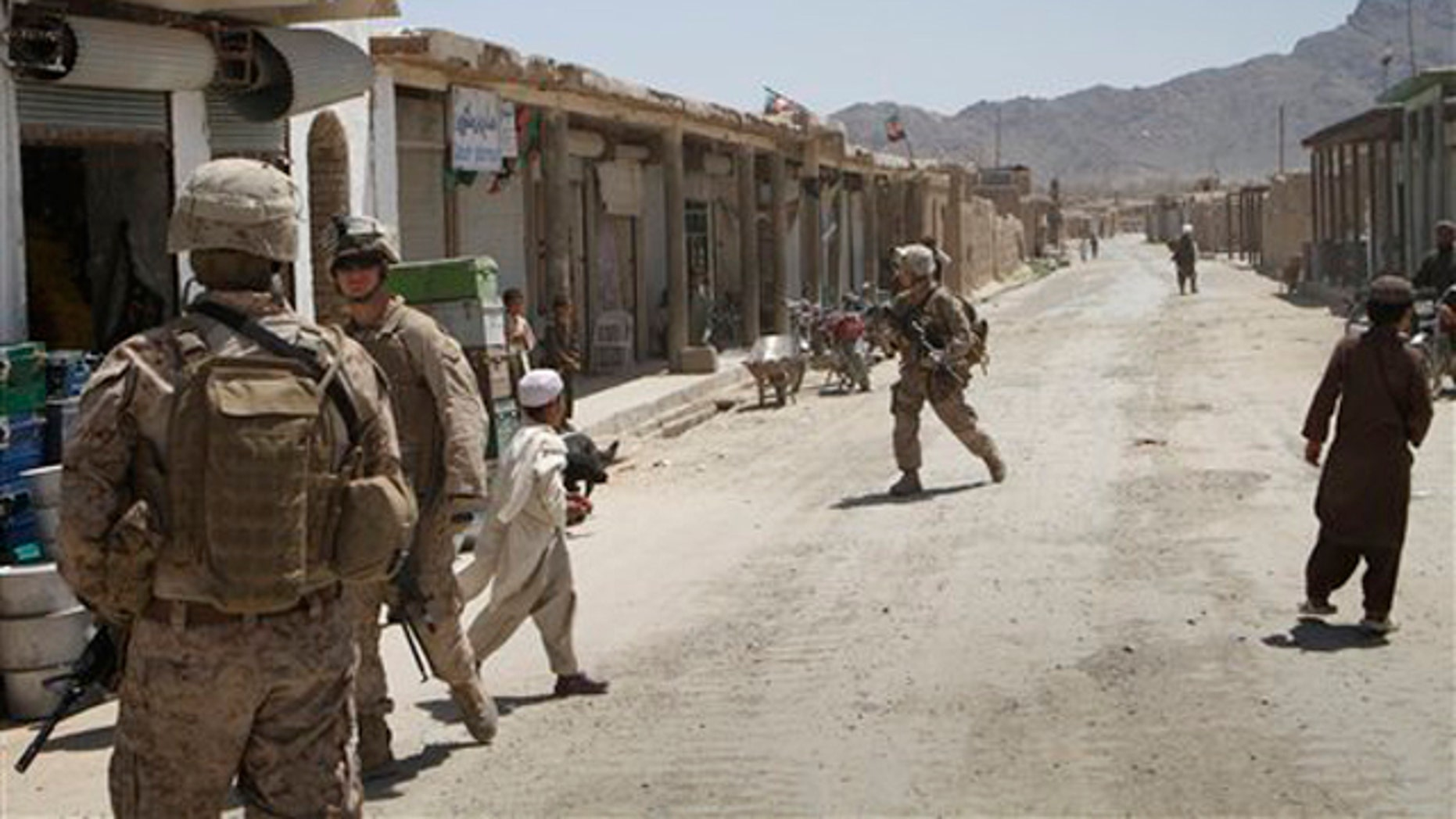 In this April 26 photo, U.S. Marines with the 3rd Battalion, 2nd Regiment patrol Nawzad's virtually empty bazaar in Helmand province south of Kabul, Afghanistan.