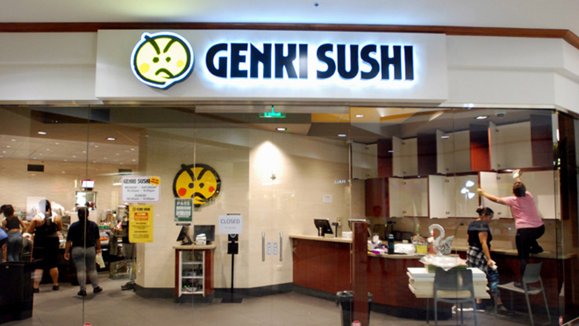 Employees clean the Genki Sushi conveyor belt restaurant chain Tuesday, Aug. 16, 2016, in Aiea, Hawaii.
