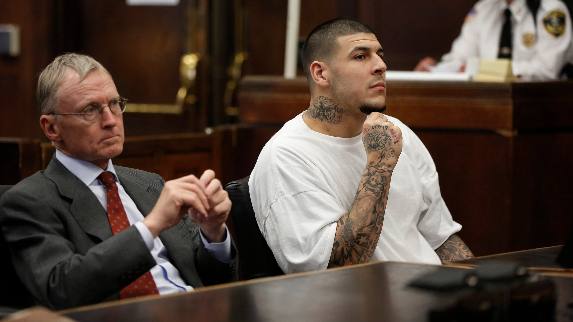 Former New England Patriots NFL football player Aaron Hernandez, center, sits with defense attorney Charles Rankin, left, while attending a pre-trial hearing at Suffolk Superior Court, Tuesday, Dec. 22, 2015, in Boston. Hernandez is charged with killing two Boston men in 2012 after a chance encounter at a nightclub. (AP Photo/Steven Senne, Pool)