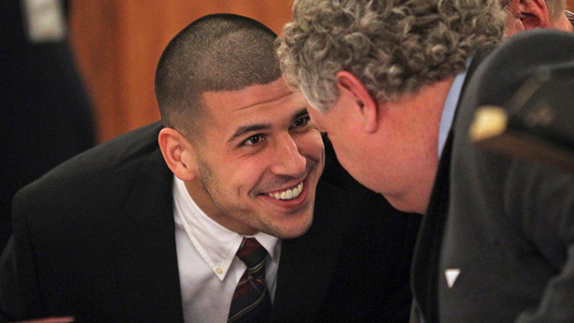FILE 2013: Former New England Patriots player Aaron Hernandez smiles at his defense attorney Michael Fee  as he appears in court at the Fall River Justice Center in Fall River, Mass.
