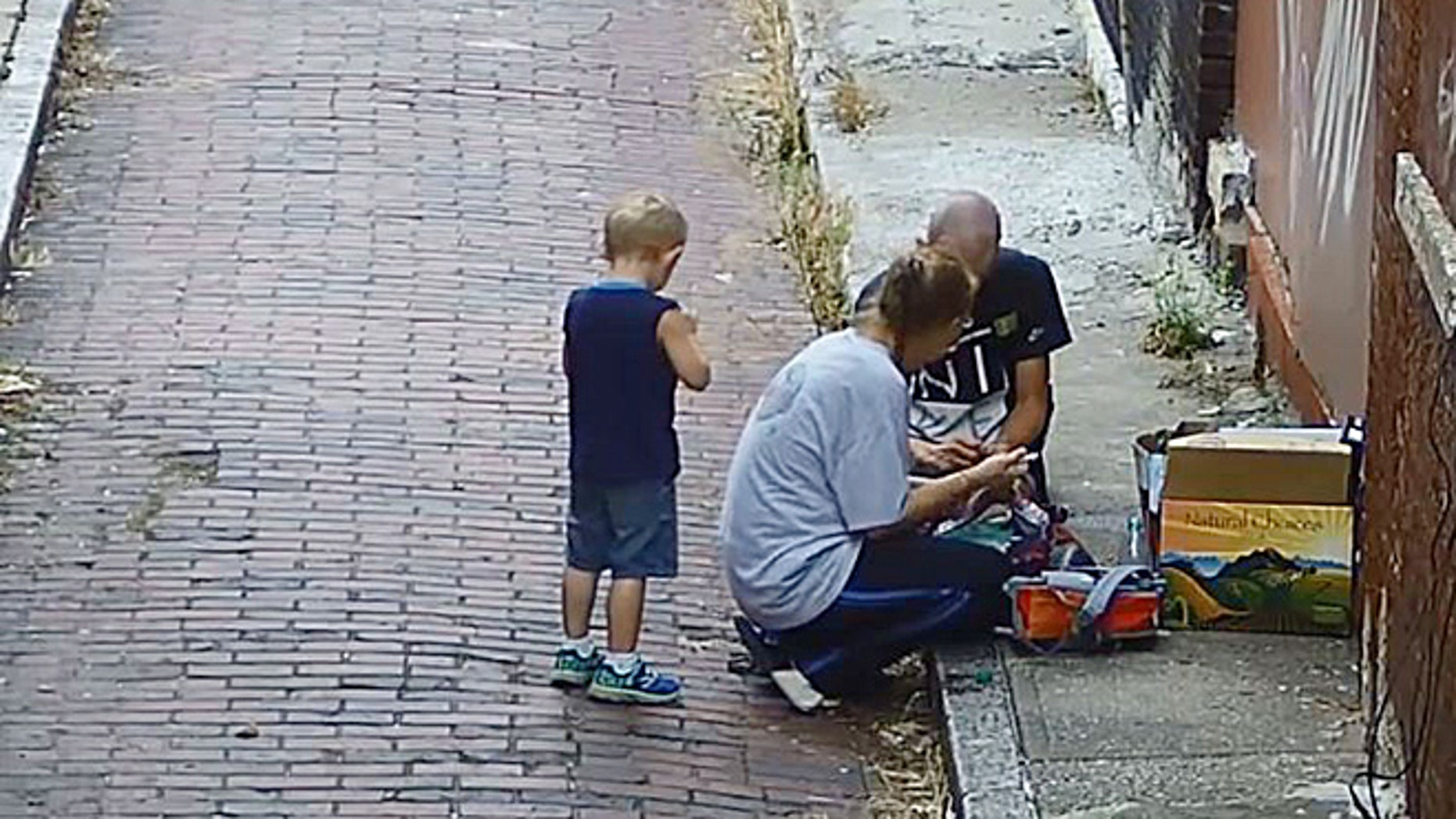 Image from surveillance video that cops say shows a mom shooting up in front of her 4-year-old son.