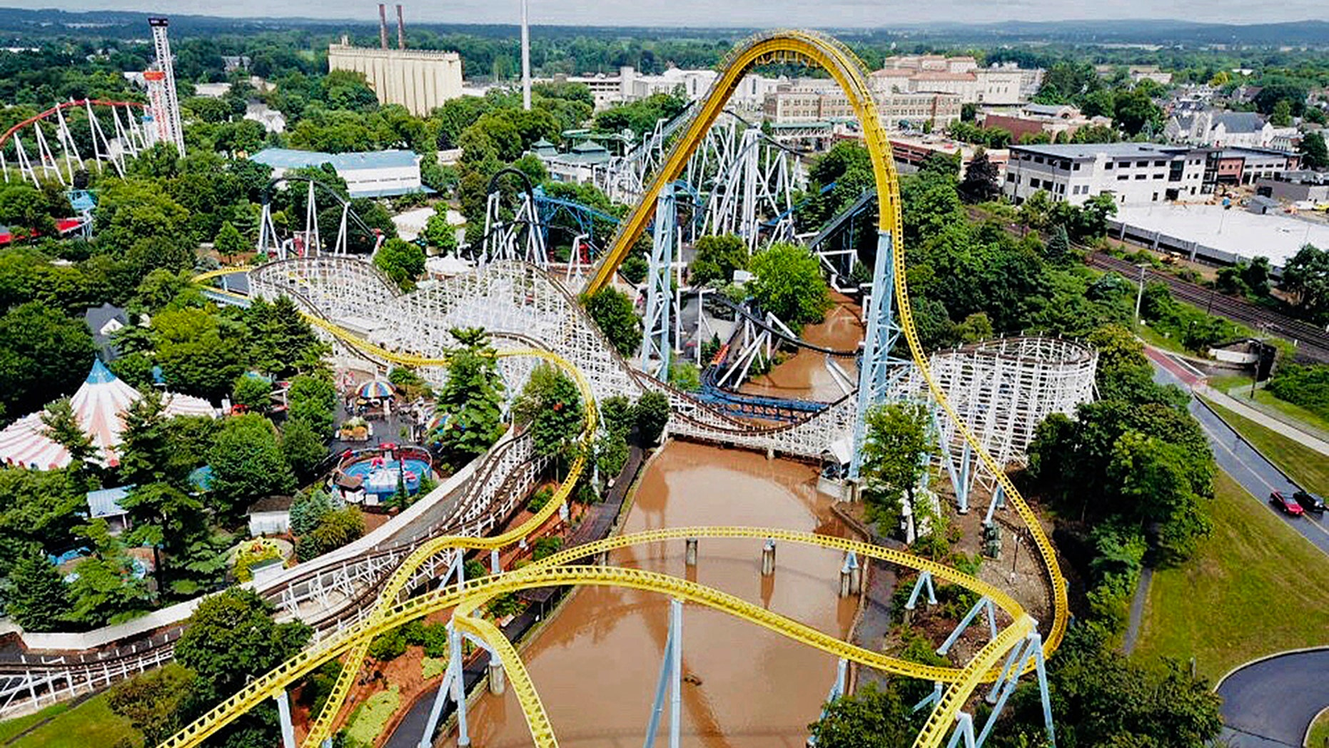 In this Monday, July 23, 2018, aerial image provided by The Wyse Choice photography in Hershey, Pa., muddy brown floodwaters in Spring Creek flow beneath the Skyrush roller coaster, in yellow.