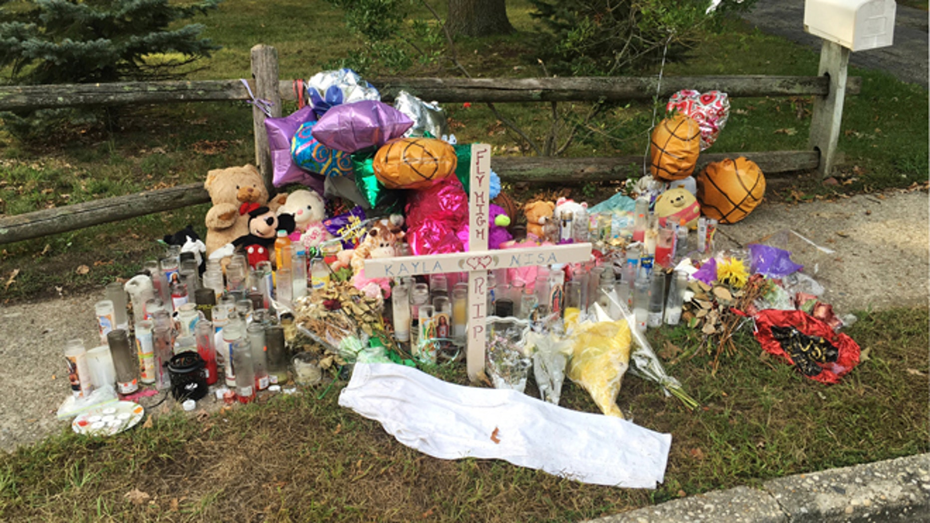 In this Sept. 27, 2016 photo, a memorial for Nisa Mickens and Kayla Cueva is located near the locations where their bodies were found in Brentwood, N.Y. The girls, who were best friends, were found murdered. Multiple teenagers from the same Long Island high school have been found dead and while police suspect all the deaths are related to gang violence, they are releasing few details.