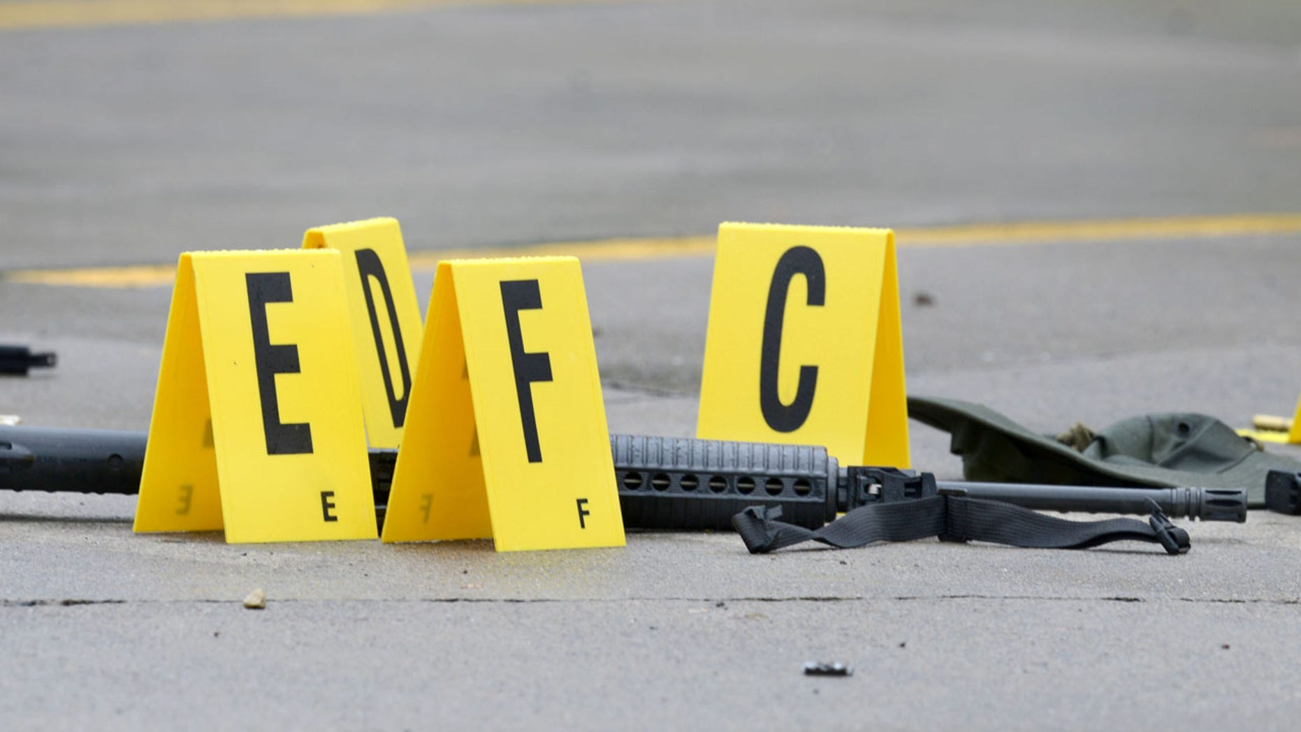 July 7, 2016: A weapon lays on the ground next to evidence markers in Bristol, Tenn. Three people were injured and one person was killed after a man opened fire on motorists traveling along a parkway in East Tennessee.