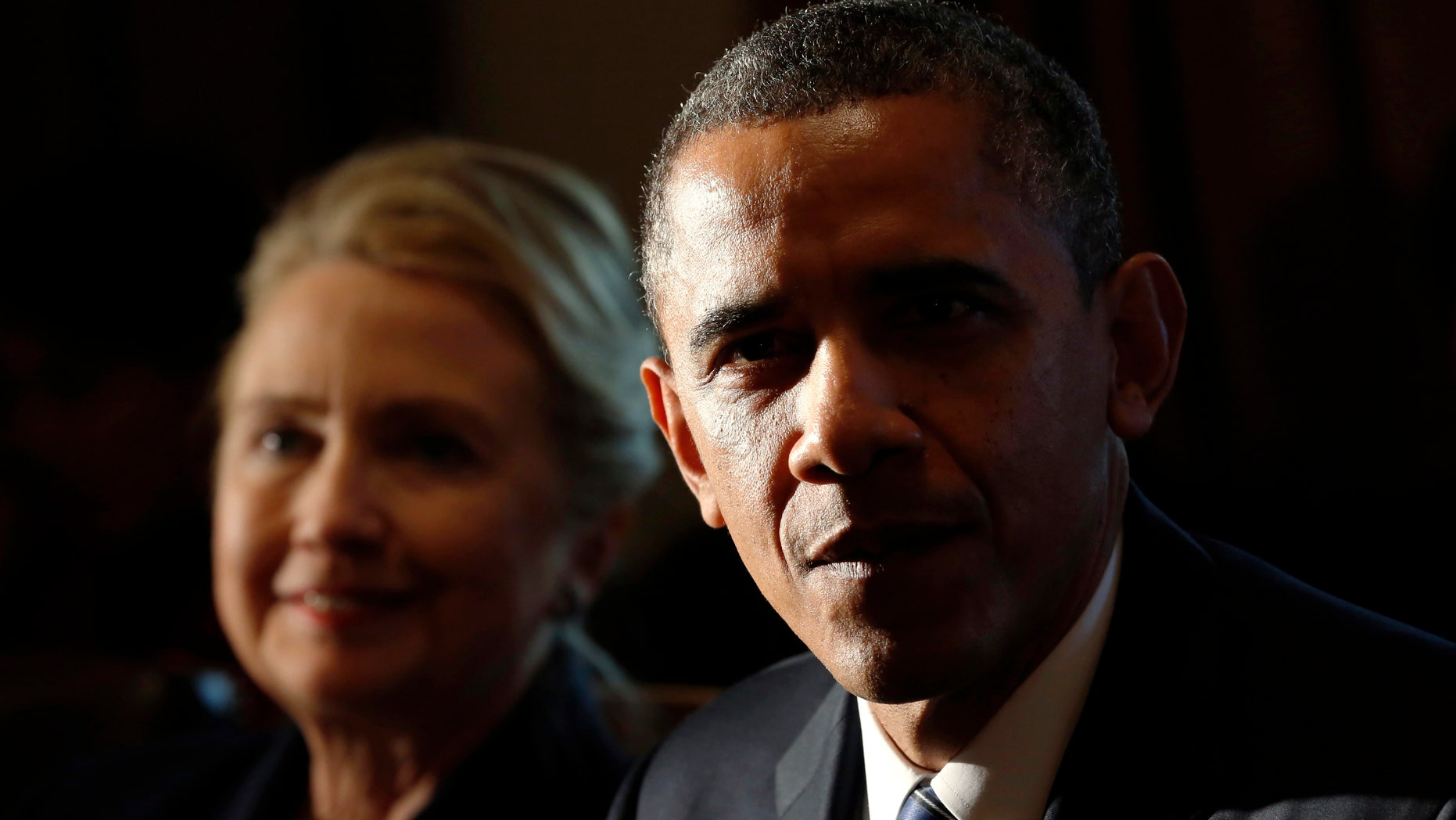FILE -- President Barack Obama speaks during a meeting with members of his cabinet at the White House in Washington Nov. 28, 2012. Seated beside him is Secretary of State Hillary Clinton. (REUTERS/Kevin Lamarque)