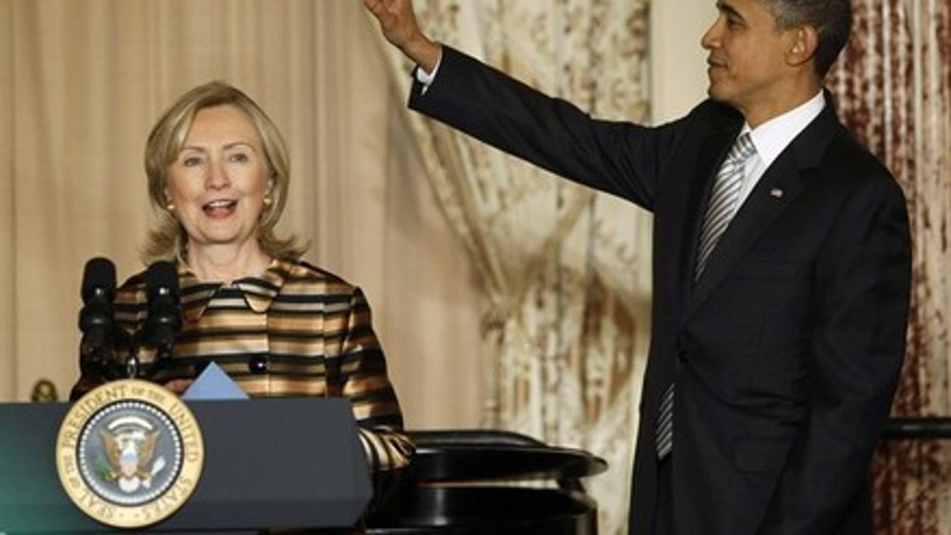 Dec. 13: President Obama waves at guests as Secretary of State Hillary Clinton introduces him to speak at a holiday reception for diplomats and state department employees at the State Department in Washington.