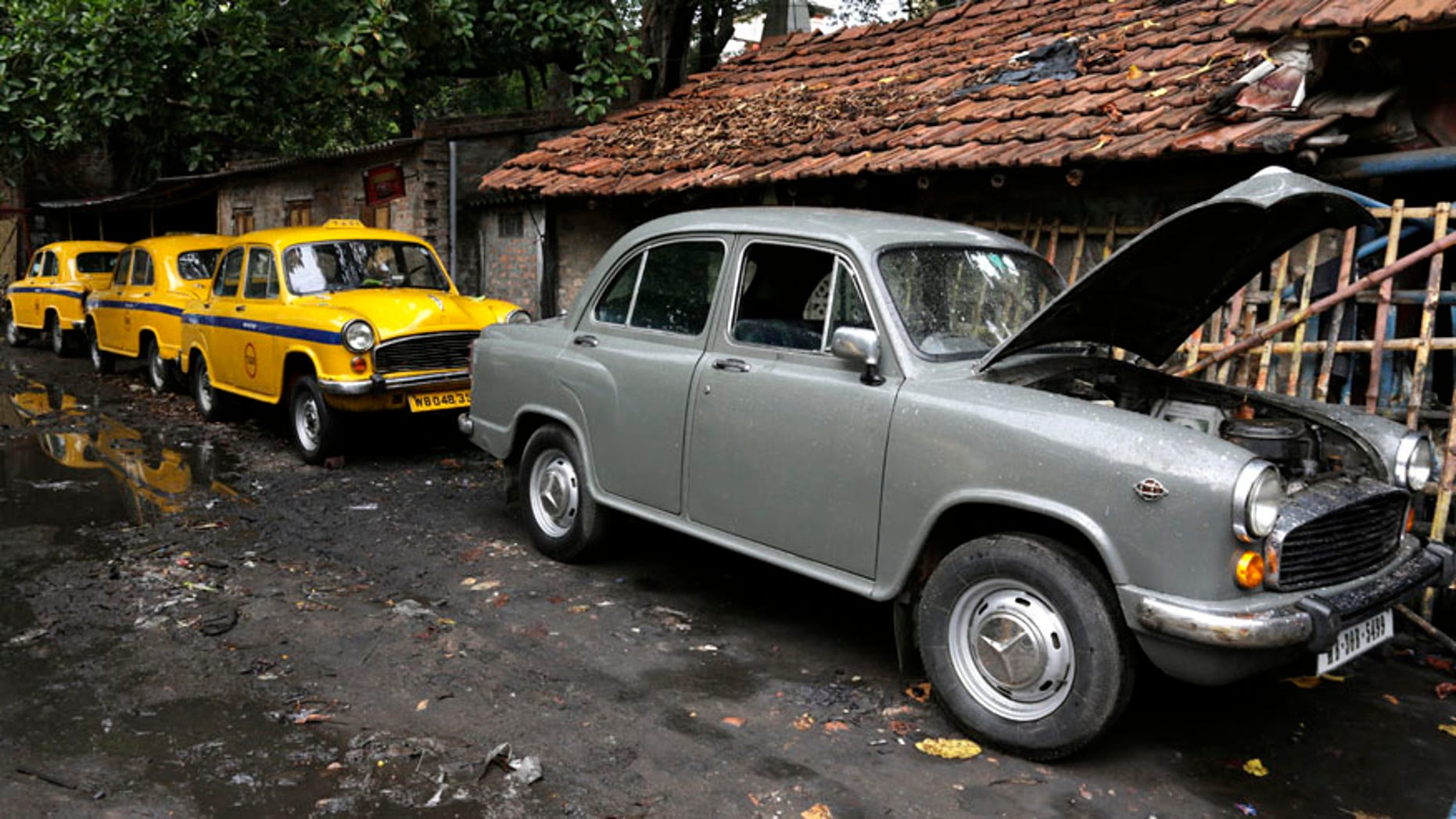 Ambassador cars, both taxis, in yellow and one private, are parked near a workshop for repairs in Kolkata, india, Monday, May 26, 2014. India's oldest car factory has abruptly suspended production of the hulking Ambassador sedan that has a nearly seven-decade history as the car of the Indian elite. (AP Photo/ Bikas Das)