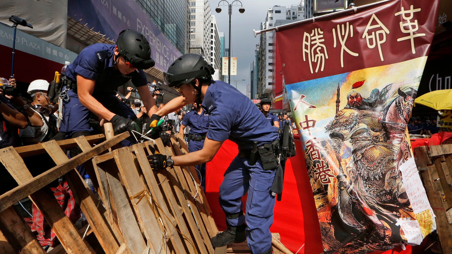 Nov. 26, 2014: Police officers remove the barricades made up mostly of wooden pallets by demonstrators decorated with a banner